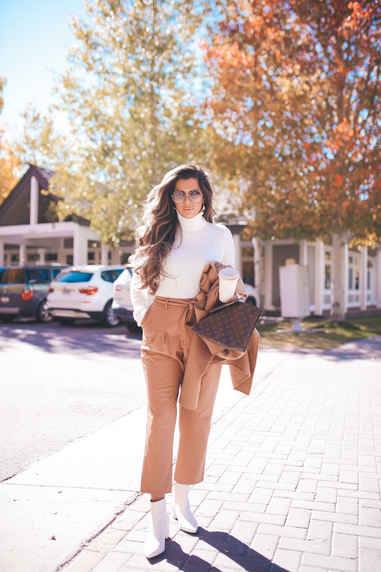 fall fashion outifit ideas pinterest 2020, fall fashion express 2020, fall outfits white booties, emily gemma |Fall Outfits by popular US fashion blog, The Sweetest Thing: image of Emily Gemma outside in Jackson Hole and wearing a Express Wide Ribbed Turtleneck Sweater, Express Super High Waisted Vegan Leather Belted Ankle Pant, Express Snakeskin Textured Block Heel Booties, Express Small Twisted Hoop Earrings, Express Belted Wrap Front Wool Coat and Express Octagon Cut-Out Sunglasses.