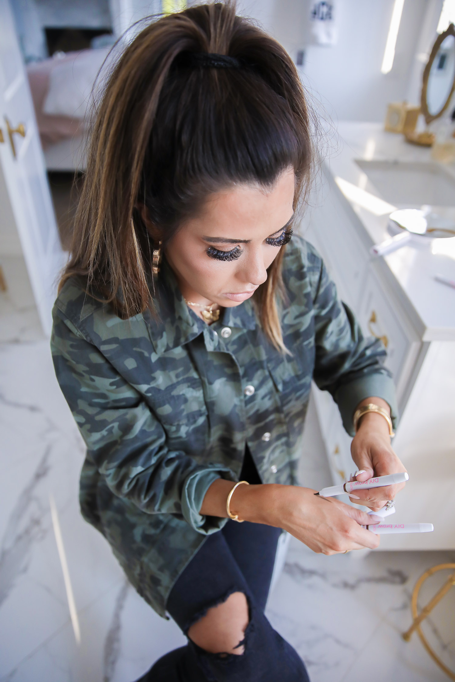 tarte DIY brow pen, national brow day, microblading brow pen, emily gemma, the sweetest thing blog |Brow Pencil by popular US beauty blog, The Sweetest Thing: image of Emily Gemma wearing a camo jacket and using a Tarte DIY brow pencil.