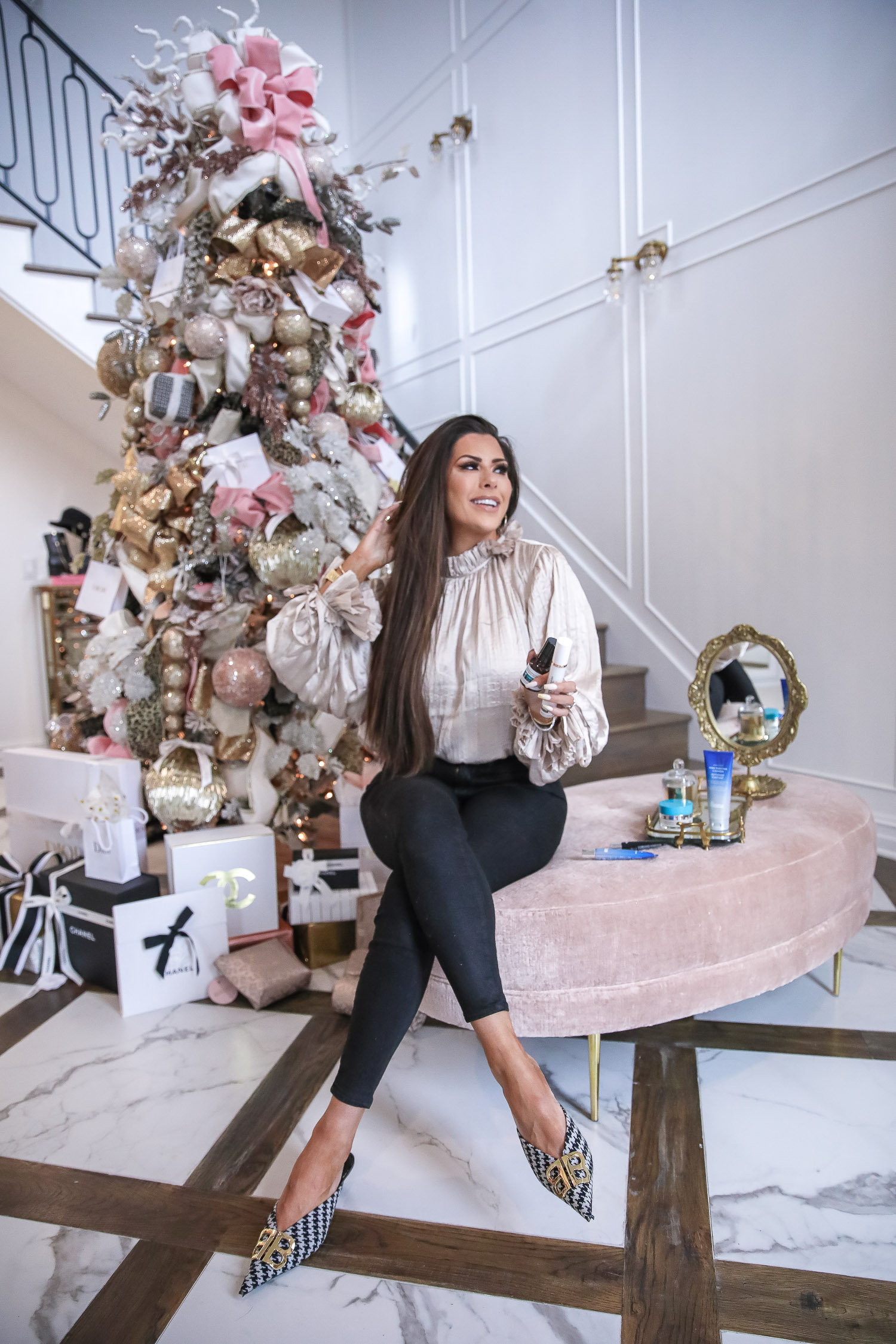Dr Brandt review eye baggage, best dr brandt products, Dr Brandt Pores No More, Emily Gemma |Dr. Brandt by popular US beauty blog, The Sweetest Thing: image of Emily Gemma sitting on pink velvet ottoman in front of a Christmas tree and holding some Dr. Brandt skincare products in her hands.