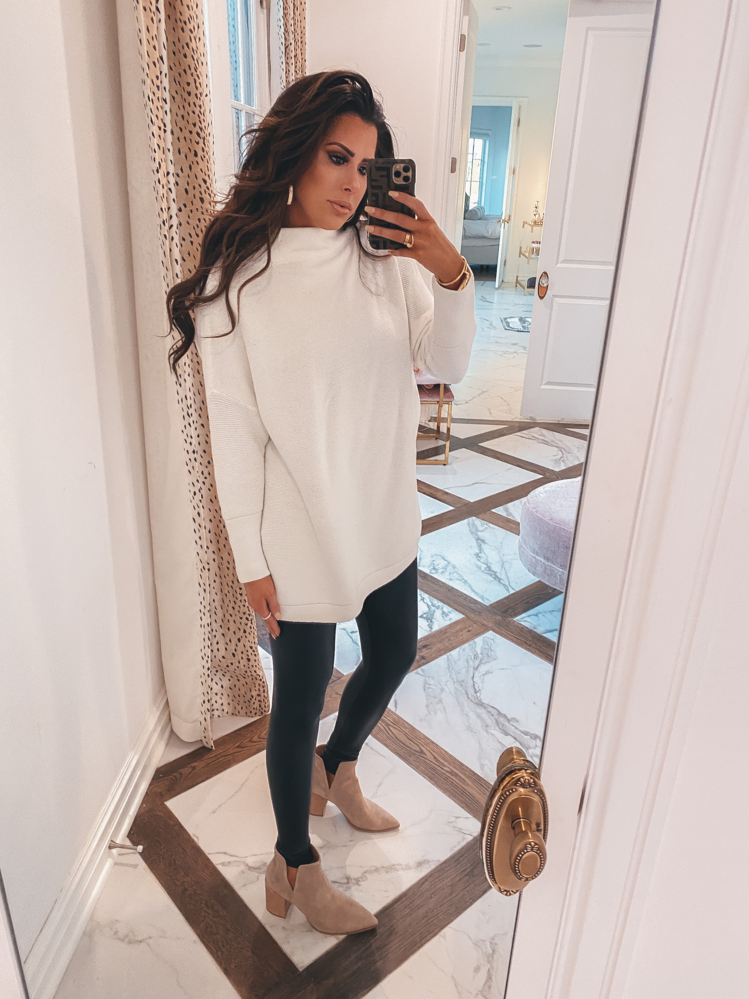 Thanksgiving Outfits by popular US fashion blog, The Sweetest Thing: image of Emily Gemma wearing a oversized cream colord mock neck sweater, Commando black leather leggings, Steve Madden Boots, Cartier rings and bracelets, Bracha necklace and The Styled Collection earrings.