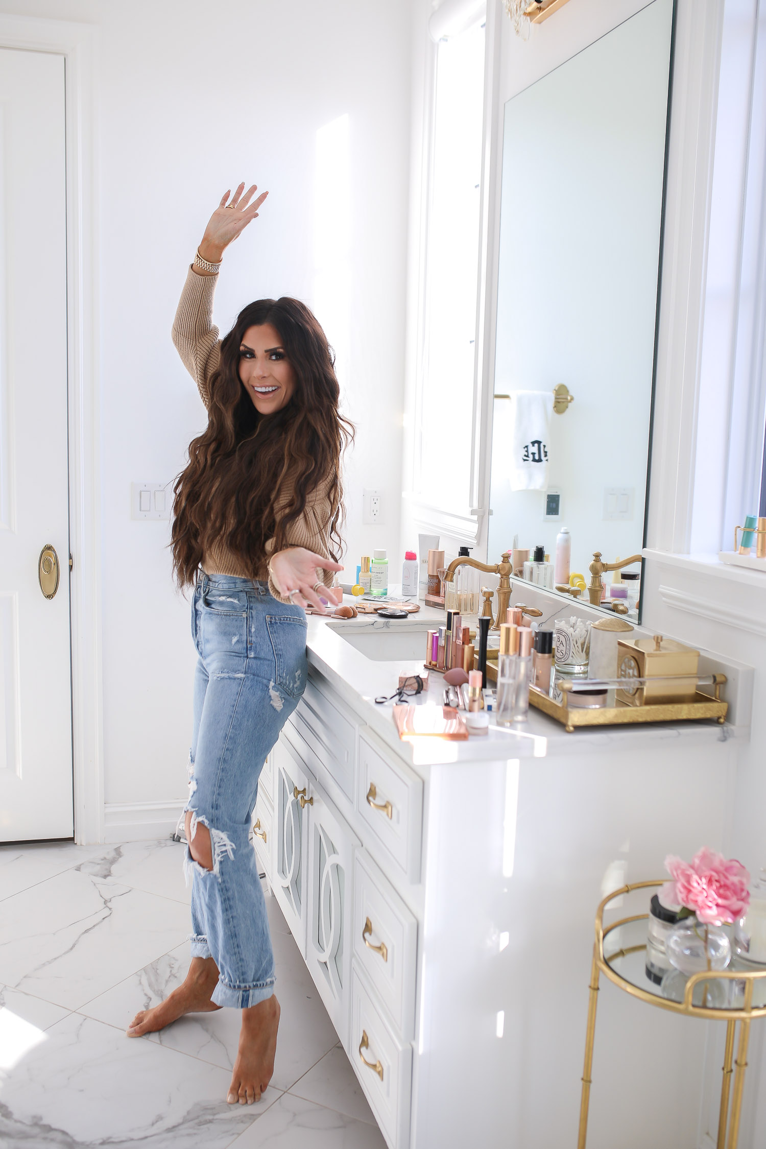 Sephora savings event fall 2020, beauty blogger sephora favorites fall 2020, emily ann gemma |Sephora Beauty Insider Sale by popular US beauty blog, The Sweetest Thing: image of Emily Gemma wearing a puff sleeve turtleneck sweater, Rolex watch, high waist distressed jeans and standing next to her vanity in her bathroom.