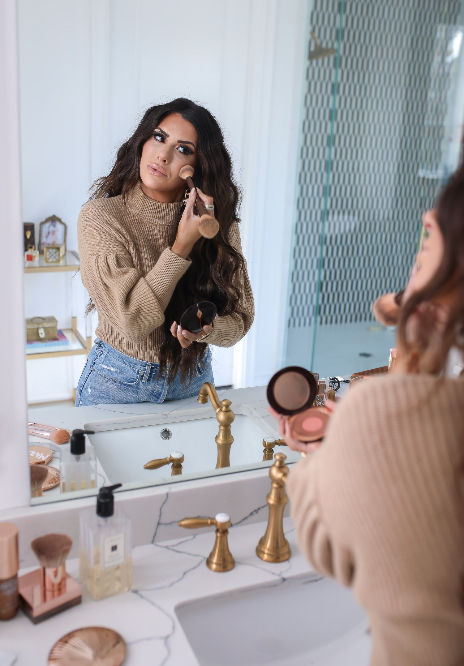 Sephora savings event fall 2020, beauty blogger sephora favorites fall 2020, emily ann gemma |Sephora Beauty Insider Sale by popular US beauty blog, The Sweetest Thing: image of Emily Gemma wearing a puff sleeve turtleneck sweater, Rolex watch, high waist distressed jeans and applying Sephora bronzer in her bathroom mirror.