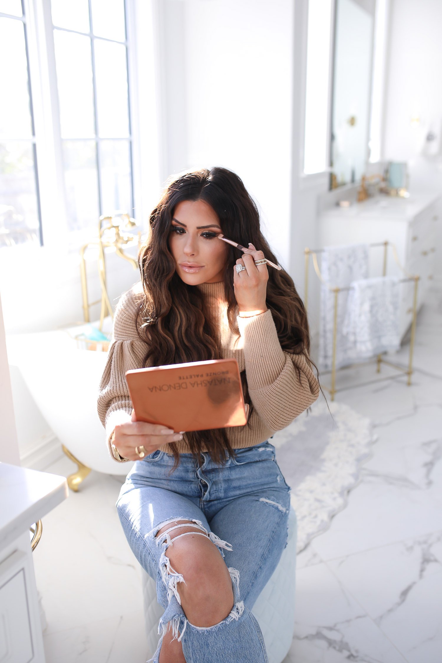 Sephora savings event fall 2020, beauty blogger sephora favorites fall 2020, emily ann gemma |Sephora Beauty Insider Sale by popular US beauty blog, The Sweetest Thing: image of Emily Gemma wearing a puff sleeve turtleneck sweater, Rolex watch, high waist distressed jeans and sitting on a white stool as she applies some eyeshadow.