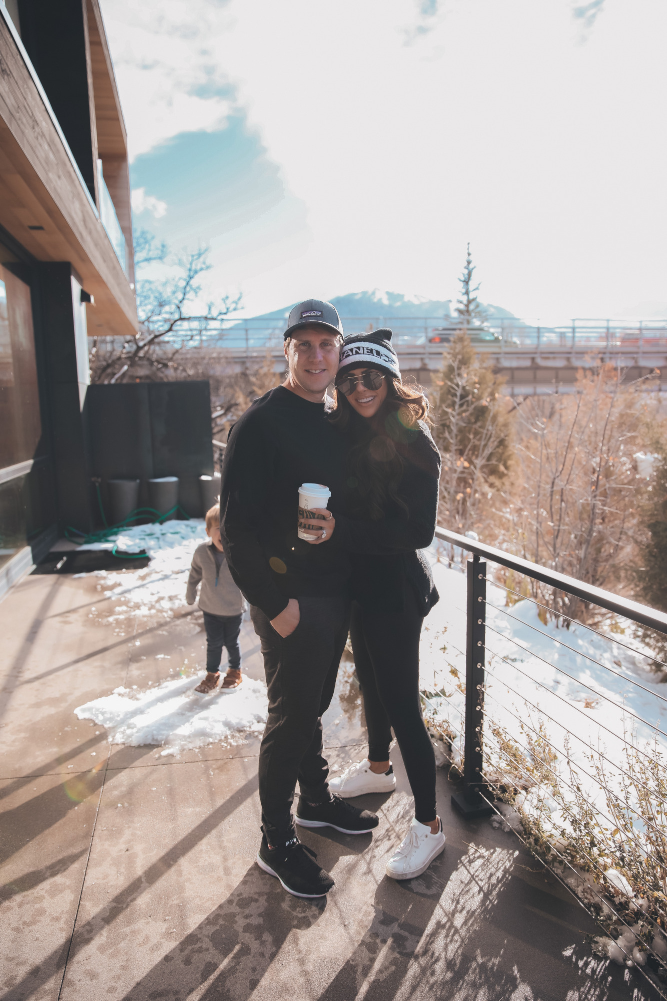 aspen fall 2020, emily gemma, John gemma, mens zella |Athleisure Wear by popular US fashion blog, The Sweetest Thing: image of a husband wearing a Logo Baseball Cap PATAGONIA, Pyrite Slim Fit Joggers ZELLA, and Crewneck Fleece Sweatshirt ZELLA, and a wife wearing a Furry Fleece Funnel Neck Pullover ZELLA, Booty Boost Active 7/8 Leggings SPANX,Charlie Platform Sneaker STEVE MADDEN,Panarea 60mm Aviator Sunglasses LE SPECS, and Lip Cheat Lip Liner CHARLOTTE TILBURY and standing together outside.