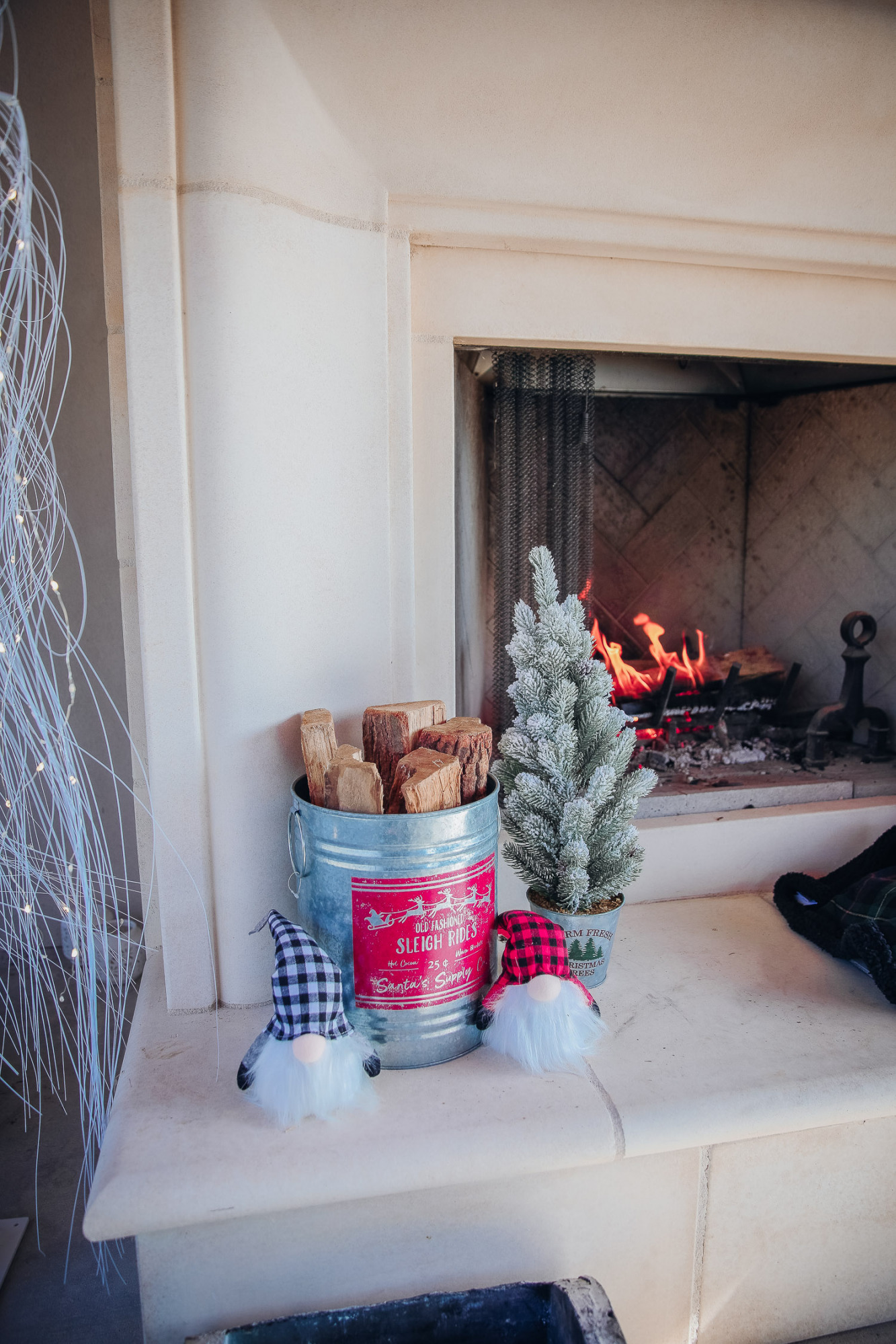 backyard decor christmas, outdoor pool christmas decor, walmart pool ornament, emily gemma backyard |Christmas Pool Decorations by popular US life and style blog, The Sweetest Thing: image of a pool house decorated with a mini flocked Christmas tree, metal bucket filled with firewood, and santa decor.