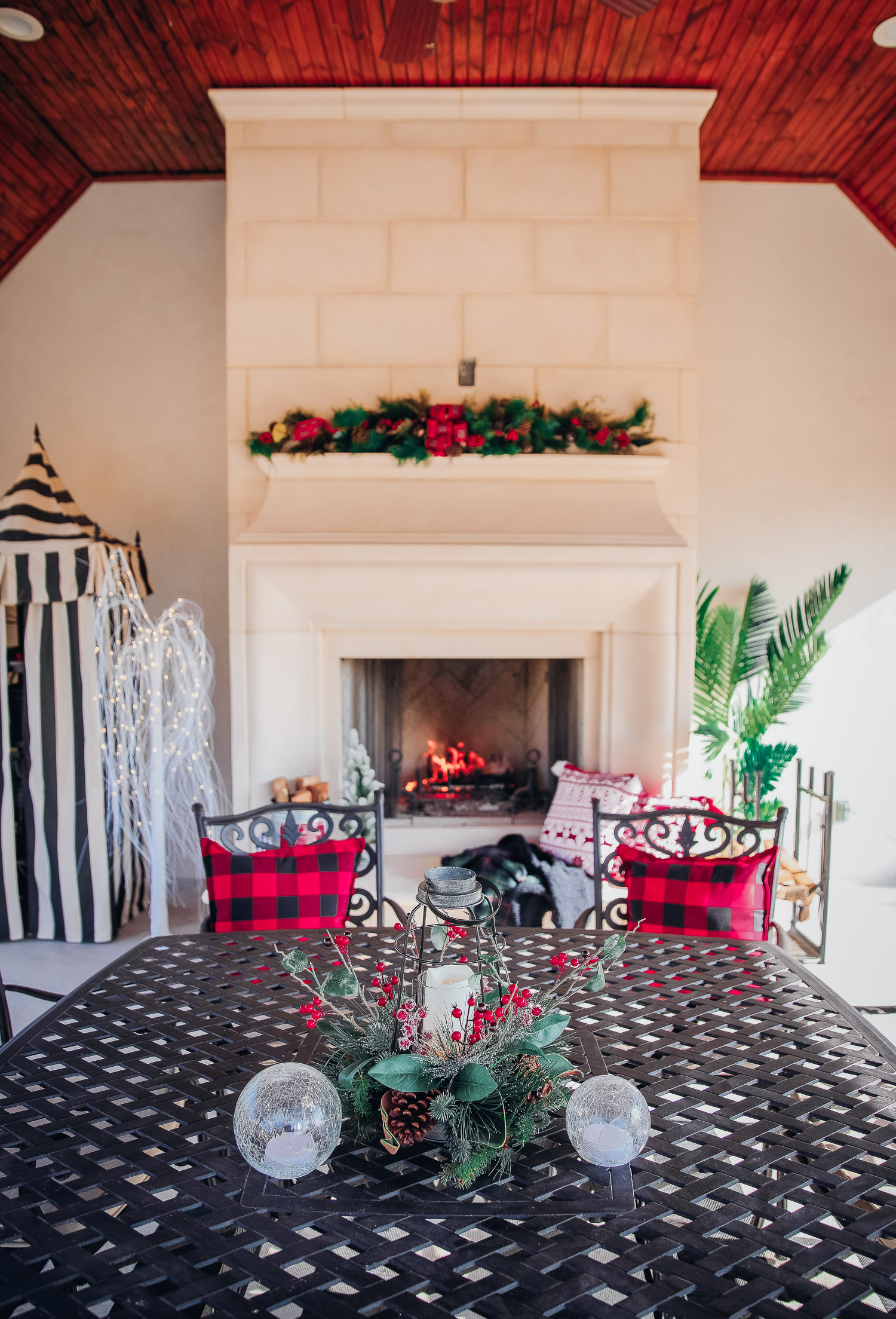 backyard decor christmas, outdoor pool christmas decor, walmart pool ornament, emily gemma backyard | Christmas Pool Decorations by popular US life and style blog, The Sweetest Thing: image of a pool house decorated with Christmas garland, black and red buffalo check throw pillows, Christmas tree decor, and candles.