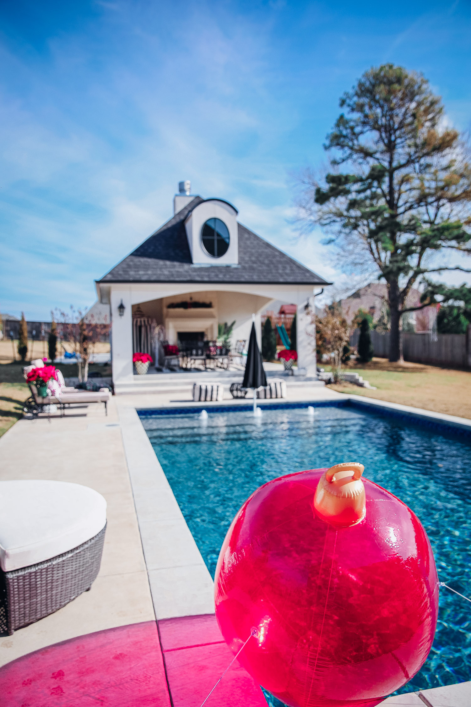 backyard decor christmas, outdoor pool christmas decor, walmart pool ornament, emily gemma backyard |Christmas Pool Decorations by popular US life and style blog, The Sweetest Thing: image of a pool house and pool decorated with Christmas garland, black and red buffalo check throw pillows, Christmas tree decor, poinsettia plants, inflatable christmas ornaments, and candles.
