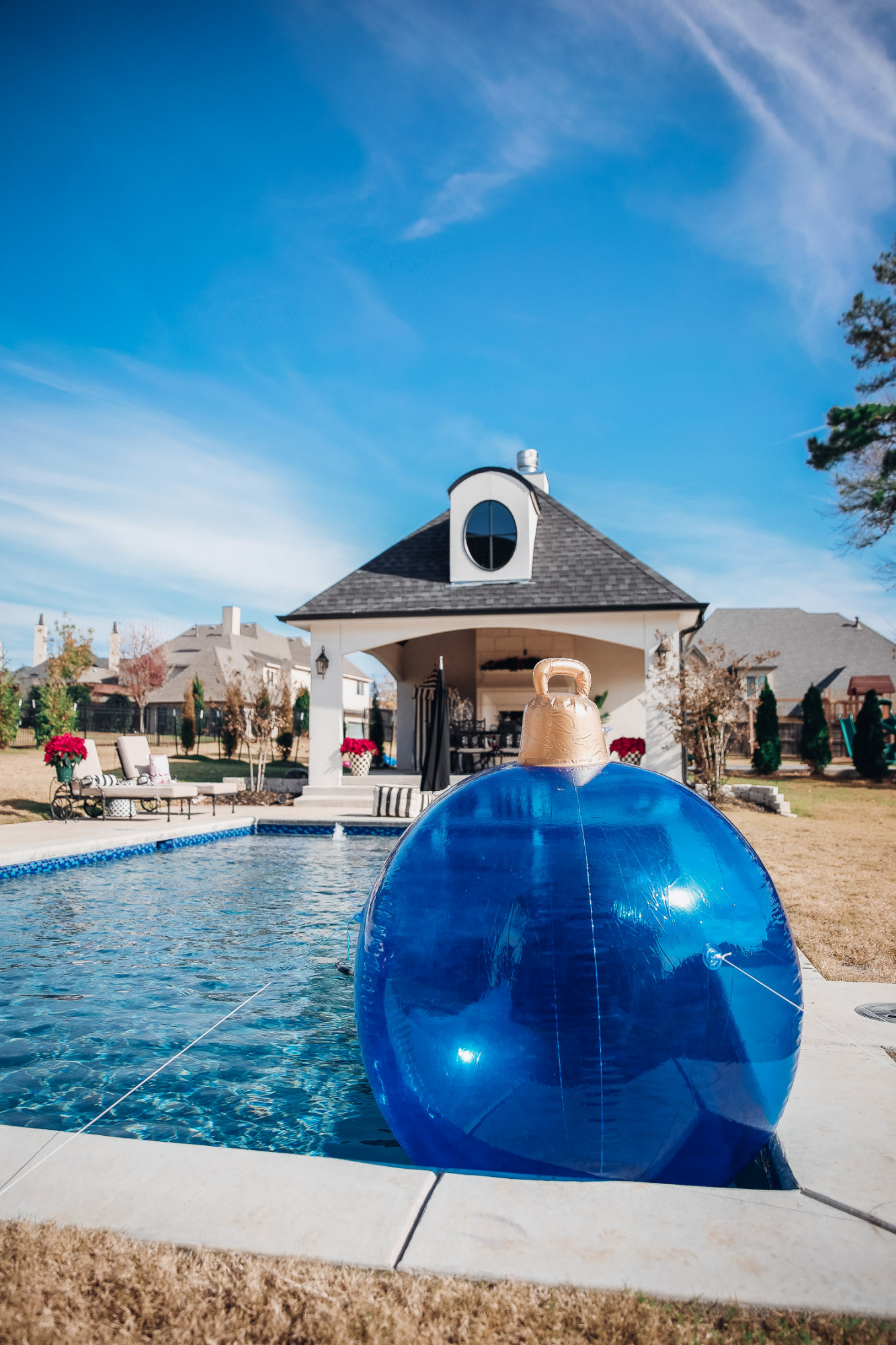 backyard decor christmas, outdoor pool christmas decor, walmart pool ornament, emily gemma backyard |Christmas Pool Decorations by popular US life and style blog, The Sweetest Thing: image of a pool house decorated with Christmas garland, black and red buffalo check throw pillows, Christmas tree decor, poinsettia plants, and inflatable Christmas ornaments.
