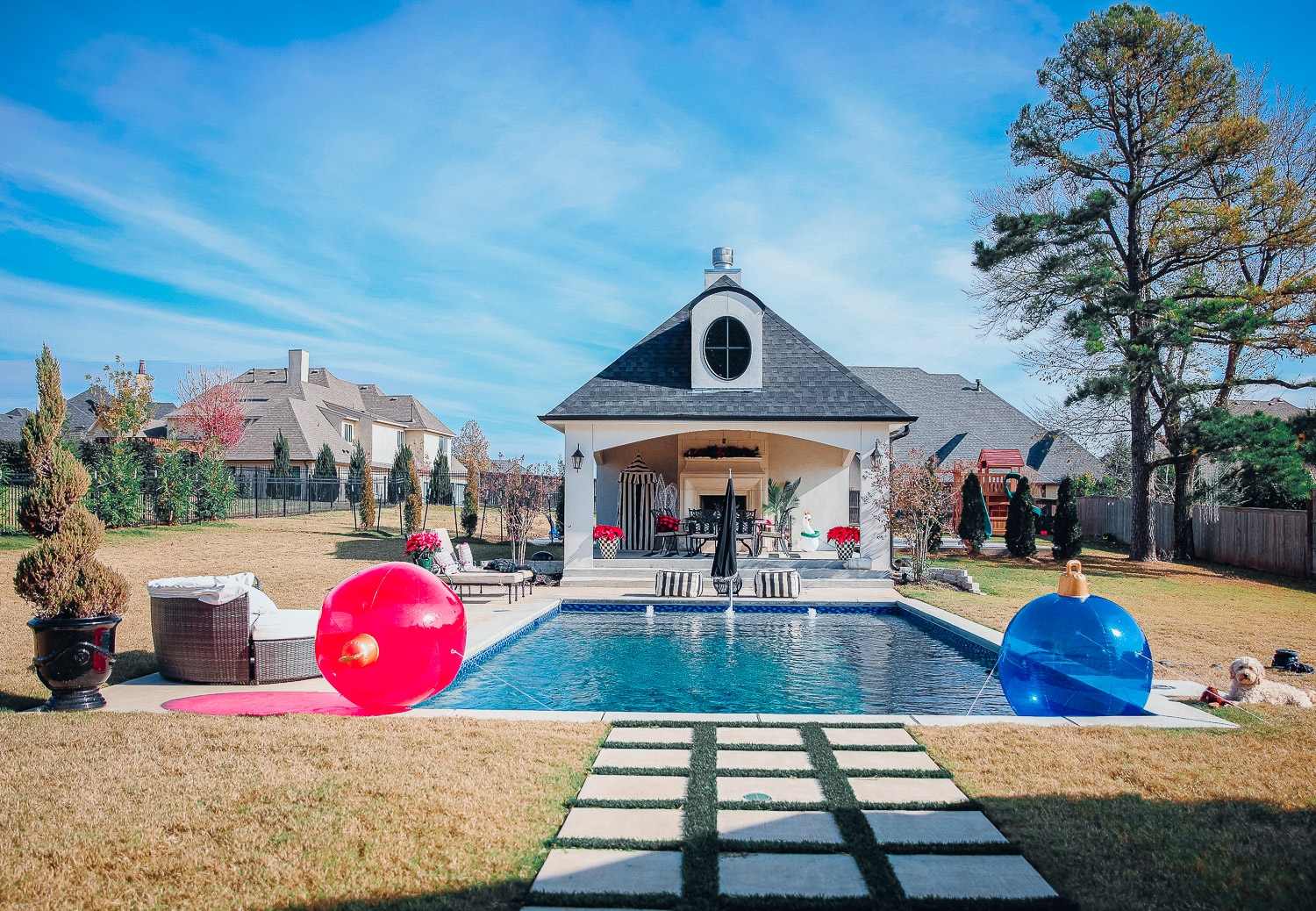 backyard decor christmas, outdoor pool christmas decor, walmart pool ornament, emily gemma backyard |Christmas Pool Decorations by popular US life and style blog, The Sweetest Thing: image of a pool house decorated with Christmas garland, black and red buffalo check throw pillows, Christmas tree decor, poinsettia plants, inflatable Christmas ornaments, and candles.