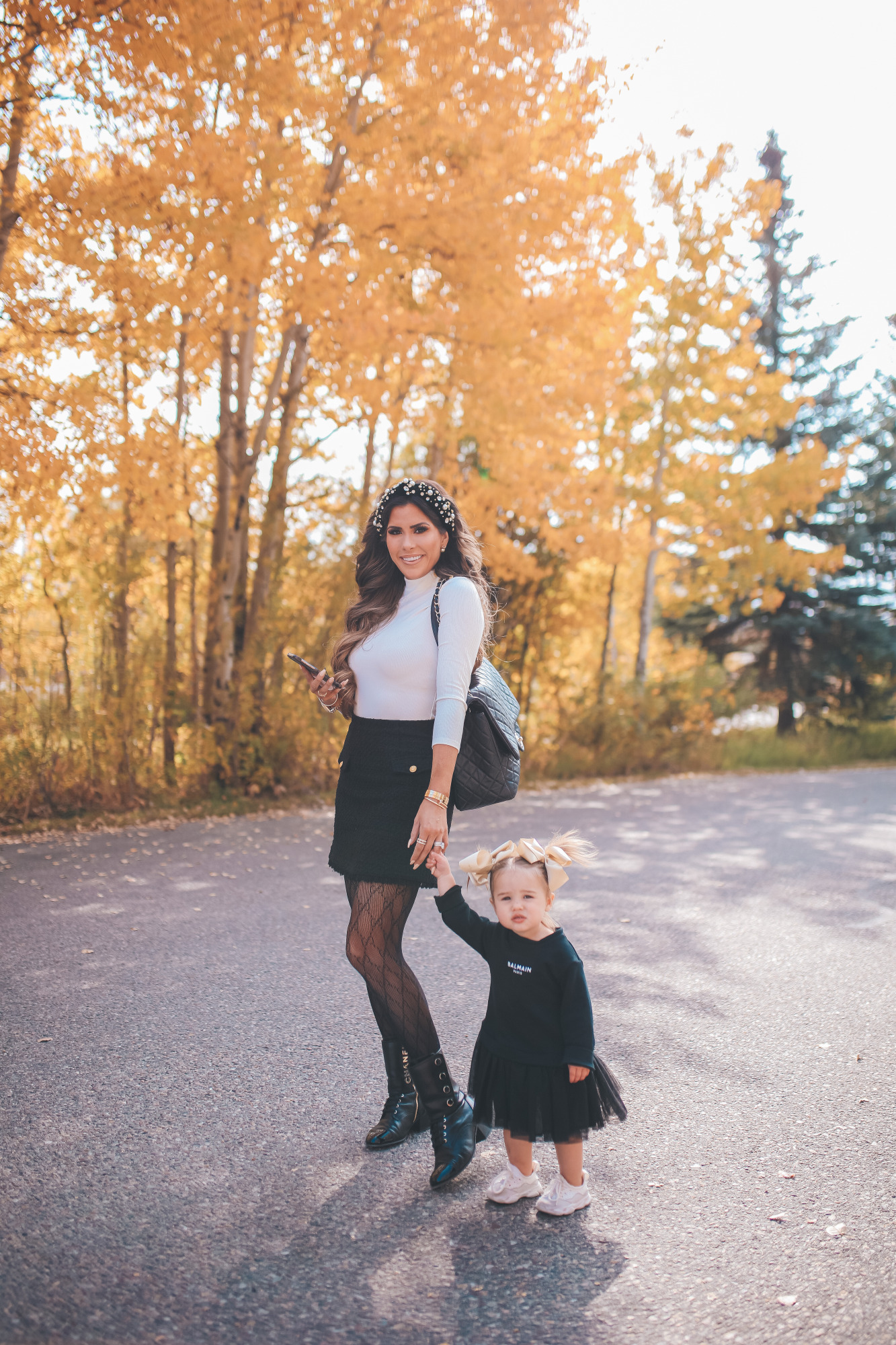 fall fashion pinterest outfits 2020, express fall fashion, emily gemma, baby girl fall outfits | Fall Clothing by popular US fashion blog, The Sweetest Thing: image of Emily Gemma walking outside and with her young daughter and wearing a Express Novelty Button Mock Neck Top, Express High Waisted A-Line Tweed Mini Skirt, Chanel boots, Gucci tights, Cartier bracelet and pearl knot headband.