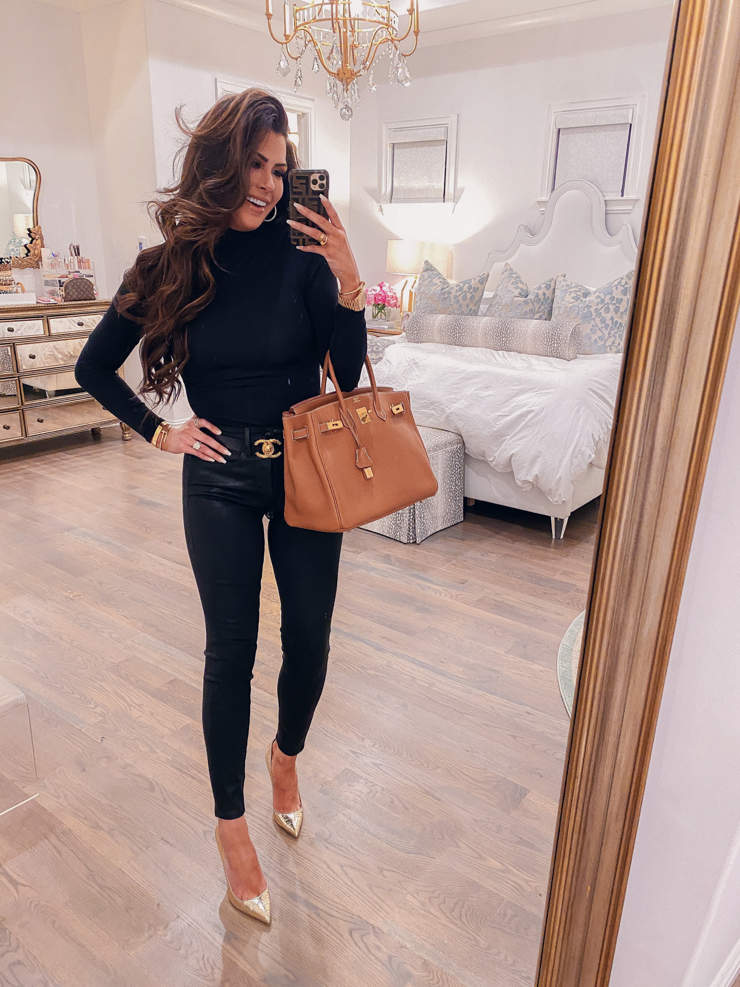flattering turtlenecks, commando turtleneck review, good american turtleneck review, emily |Holiday Makeup by popular US beauty blog, The Sweetest Thing: image of Emily Gemma wearing a black turtleneck, black denim, gold heels, Chanel belt, and holding a camel colored Hermes Birkin bag.