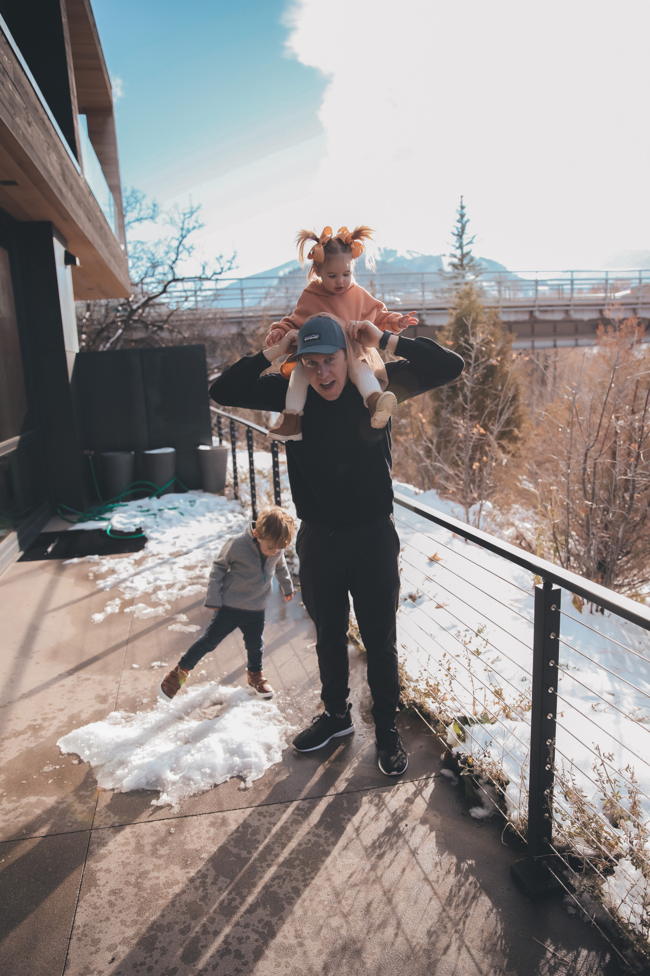 zella mens fashion, zella mens athleisure, aspen fall 2020 | Athleisure Wear by popular US fashion blog, The Sweetest Thing: image of a husband wearing a Logo Baseball Cap PATAGONIA, Pyrite Slim Fit Joggers ZELLA, and Crewneck Fleece Sweatshirt ZELLA and playing with his kids outside in the snow while his son wears a Kids' Sweater Fleece Half Zip Pullover VINEYARD VINES and a pair of UGGs.