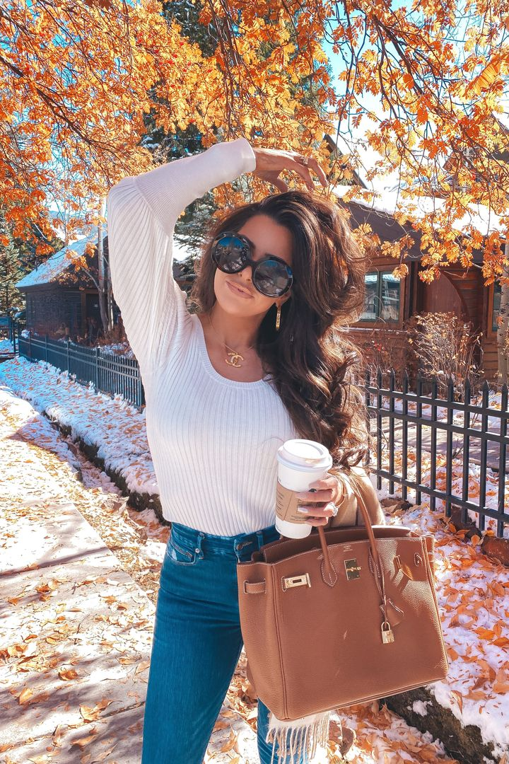 November Instagram Recap by popular US lifestyle blog, The Sweetest Thing: image of Emily Gemma wearing a Chanel necklace, Express white long sleeve top, Good American jeans, oversized sunglasses, and holding a brown Birkin bag and TopShop scarf.