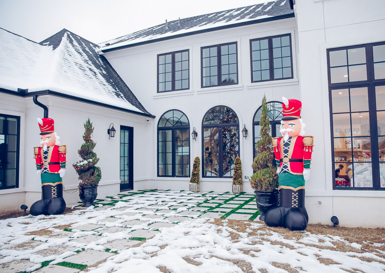 Christmas outdoor decorations home depot, emily gemma home, christmas wreaths on gates with bow, blow up nutcrackers, |Holiday Home Decor by popular US life and style blog, The Sweetest Thing: image of a backyard decorated with topiary trees, white lights, and inflatable nutcrackers.