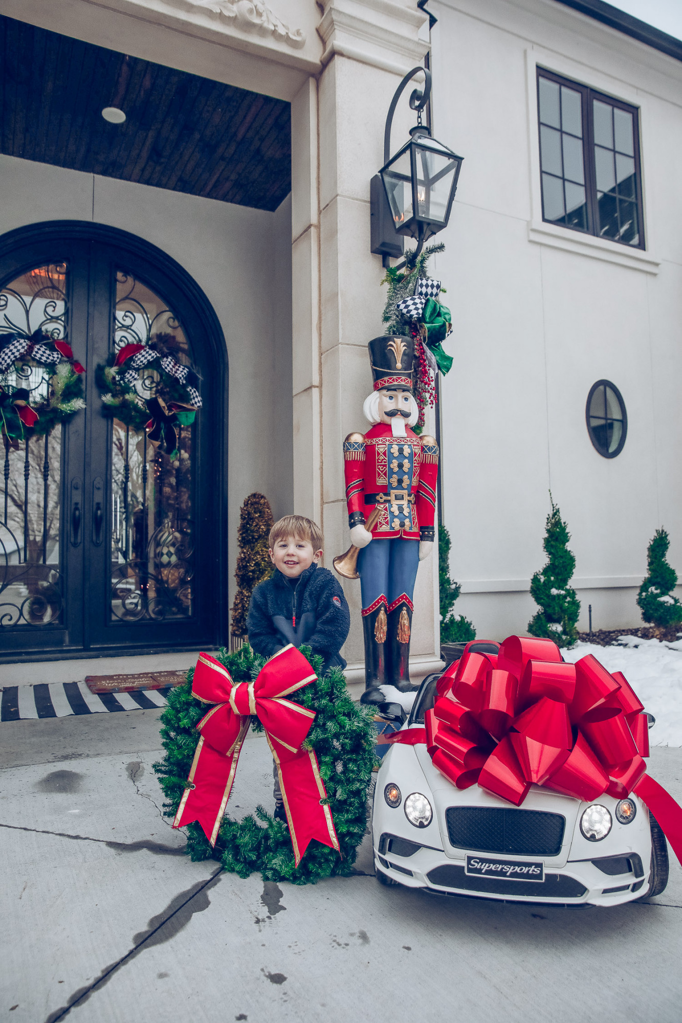 Christmas outdoor decorations home depot, emily gemma home, christmas wreaths on gates with bow, blow up nutcrackers, |Holiday Home Decor by popular US life and style blog, The Sweetest Thing: image of the front of a house decorated with nutcrackers and Christmas wreaths.
