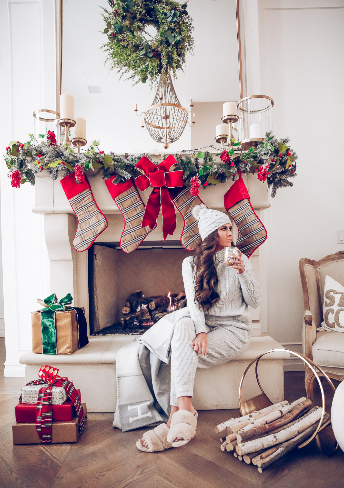 Express loungewear holiday 2020, express sweatsuit december 2020, emily gemma, holiday fireplace garland christmas | Cute Loungewear by popular US fashion blog, The Sweetest Thing: image of Emily Gemma sitting in front of a fireplace decorated with a garland, plaid stockings, and wrapped presents and wearing an Express sweater, Express pants, Express fuzzy slippers, and an Express pom beanie.