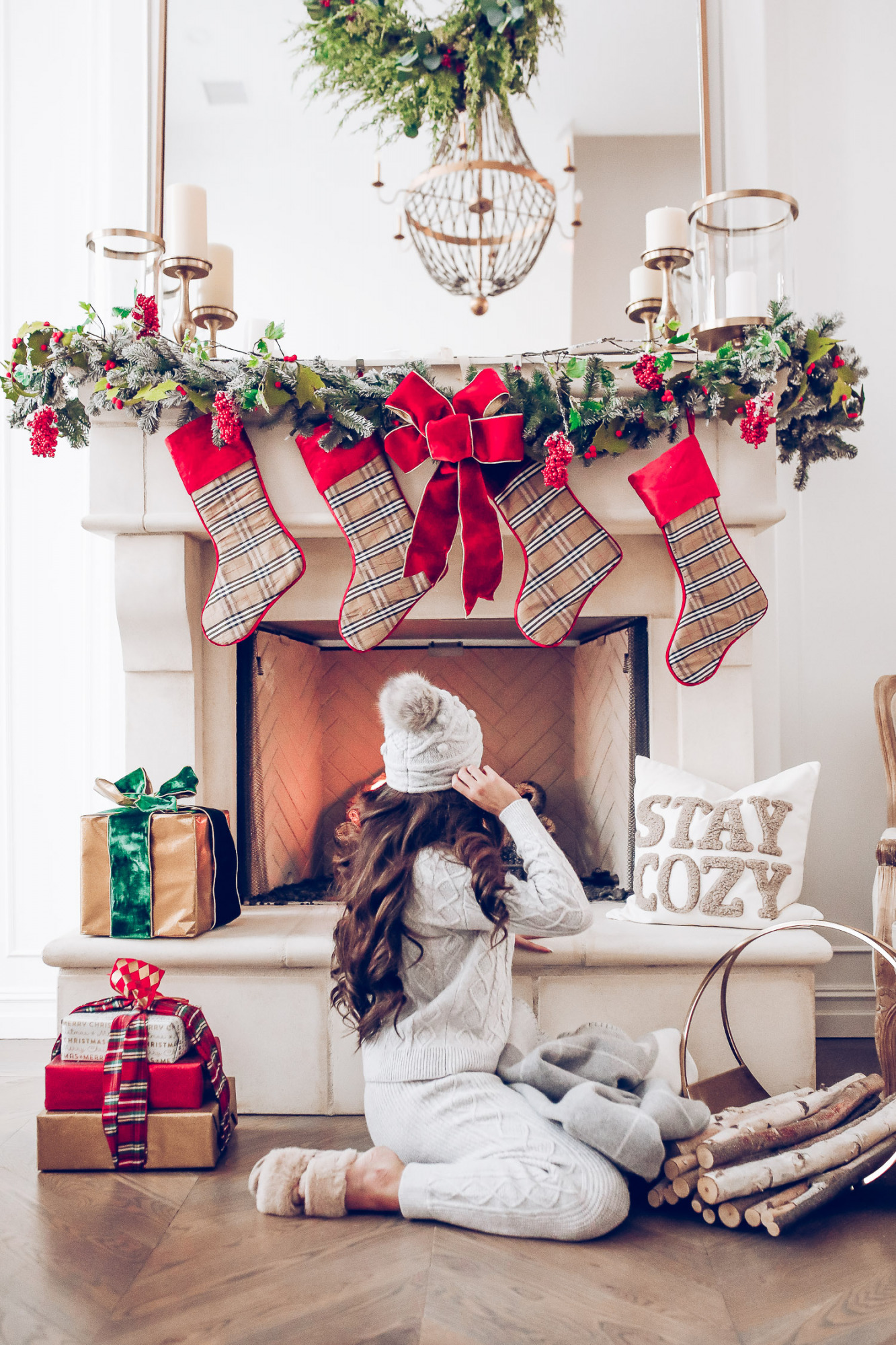Express loungewear holiday 2020, express sweatsuit december 2020, emily gemma, holiday fireplace garland christmas |Cute Loungewear by popular US fashion blog, The Sweetest Thing: image of Emily Gemma sitting in front of a fireplace decorated with a garland, plaid stockings, and wrapped presents and wearing an Express sweater, Express pants, Express fuzzy slippers, and an Express pom beanie.