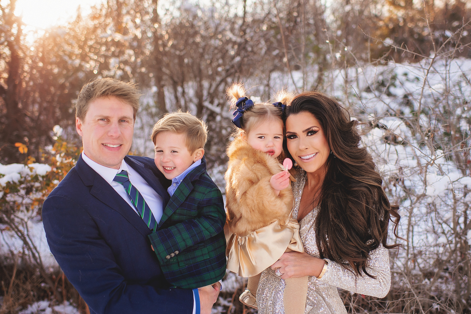 Family Christmas Card by popular US lifestyle blog, The Sweetest Thing: image of a family standing together in the snow with their dog and wearing a Eliza J sequin dress, blue suit, blue and green plaid blazer and tan pants, and a faux fur coat and gold dress.