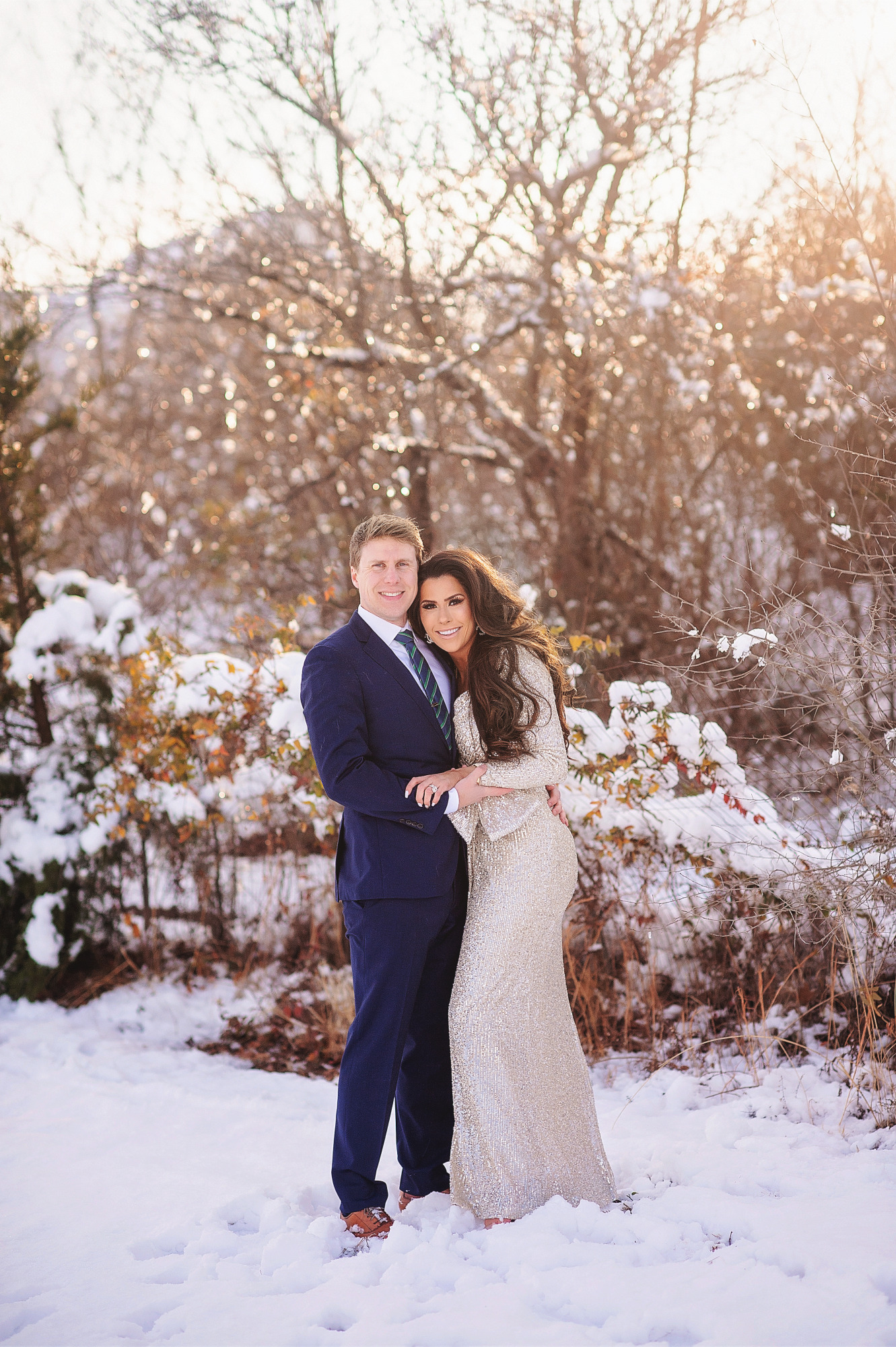 Family Christmas Card by popular US lifestyle blog, The Sweetest Thing: image of a husband and wife standing together in the snow and wearing a Eliza J sequin dress and blue suit with a blue and green stripe tie.