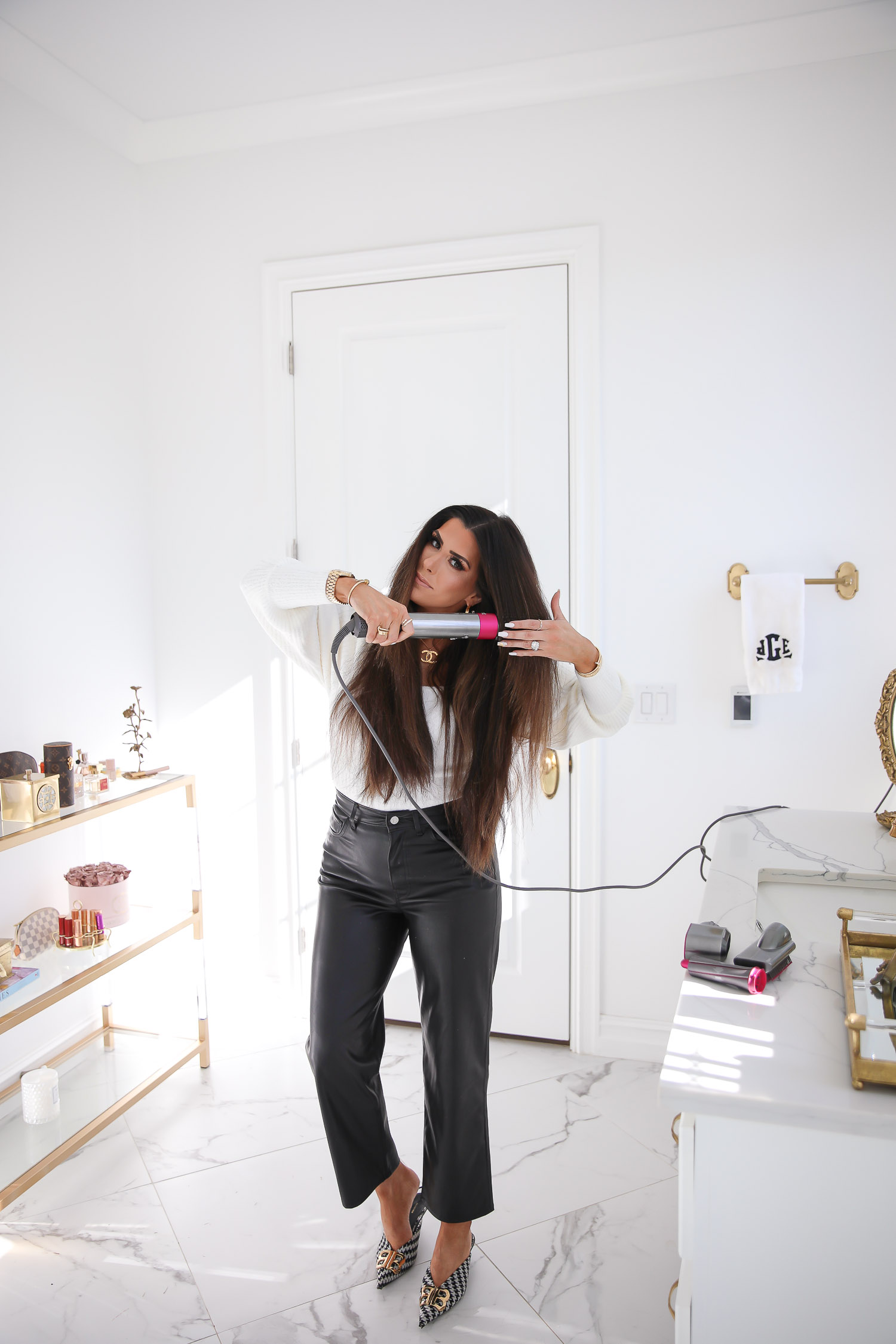 dyson airwrap review tutorial, how to curl hair with dyson air wrap, emily gemma_-4 |Dyson Air Wrap by popular US beauty blog, The Sweetest Thing: image of Emily Gemma wearing a white sweater, black faux leather pants, and Balenciaga shoes and using a Dyson Air Wrap hair styler.