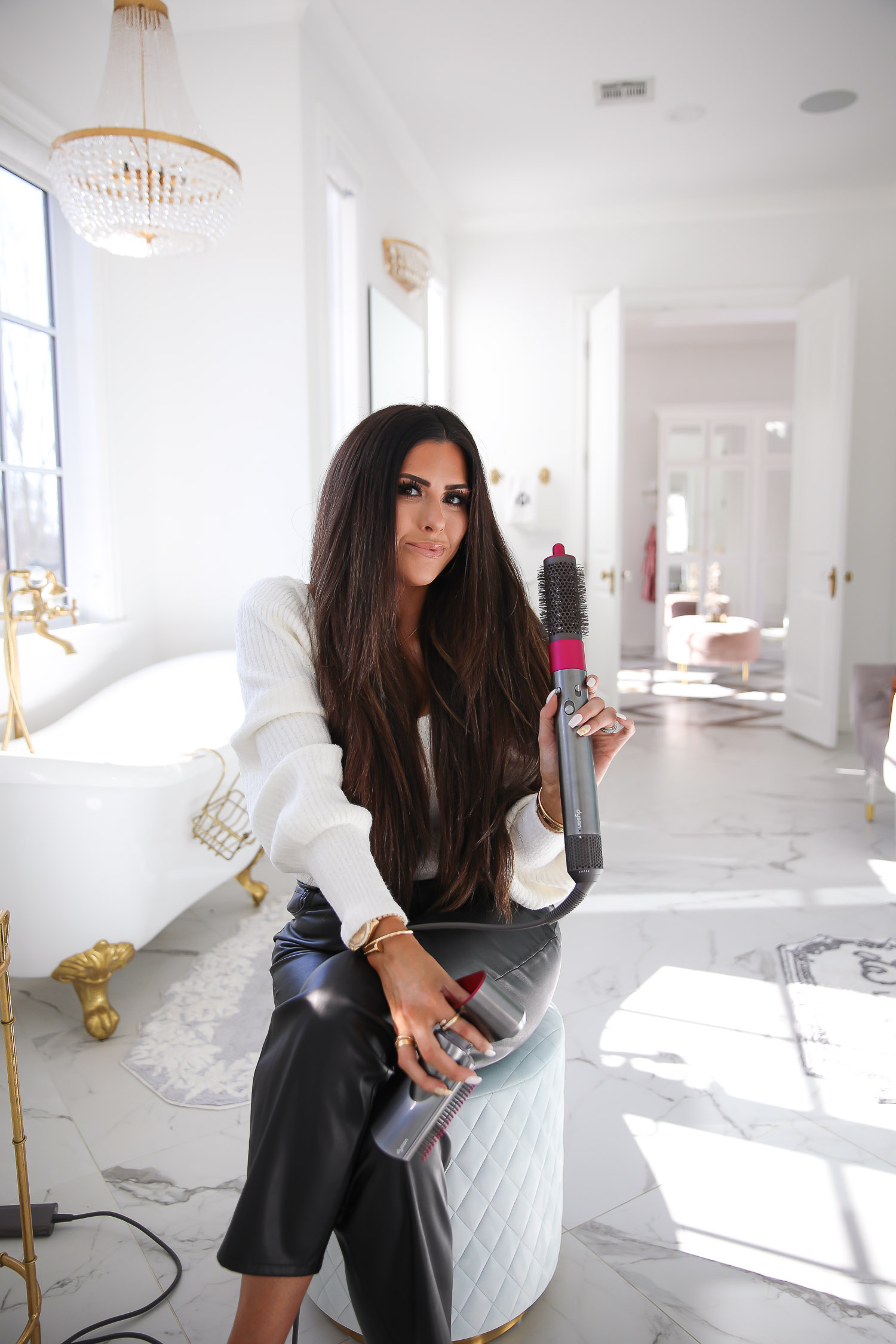 dyson airwrap review tutorial, how to curl hair with dyson air wrap, emily gemma_-4 |Dyson Air Wrap by popular US beauty blog, The Sweetest Thing: image of Emily Gemma wearing a white sweater, black faux leather pants, and Balenciaga shoes and holding a Dyson Air Wrap hair styler.