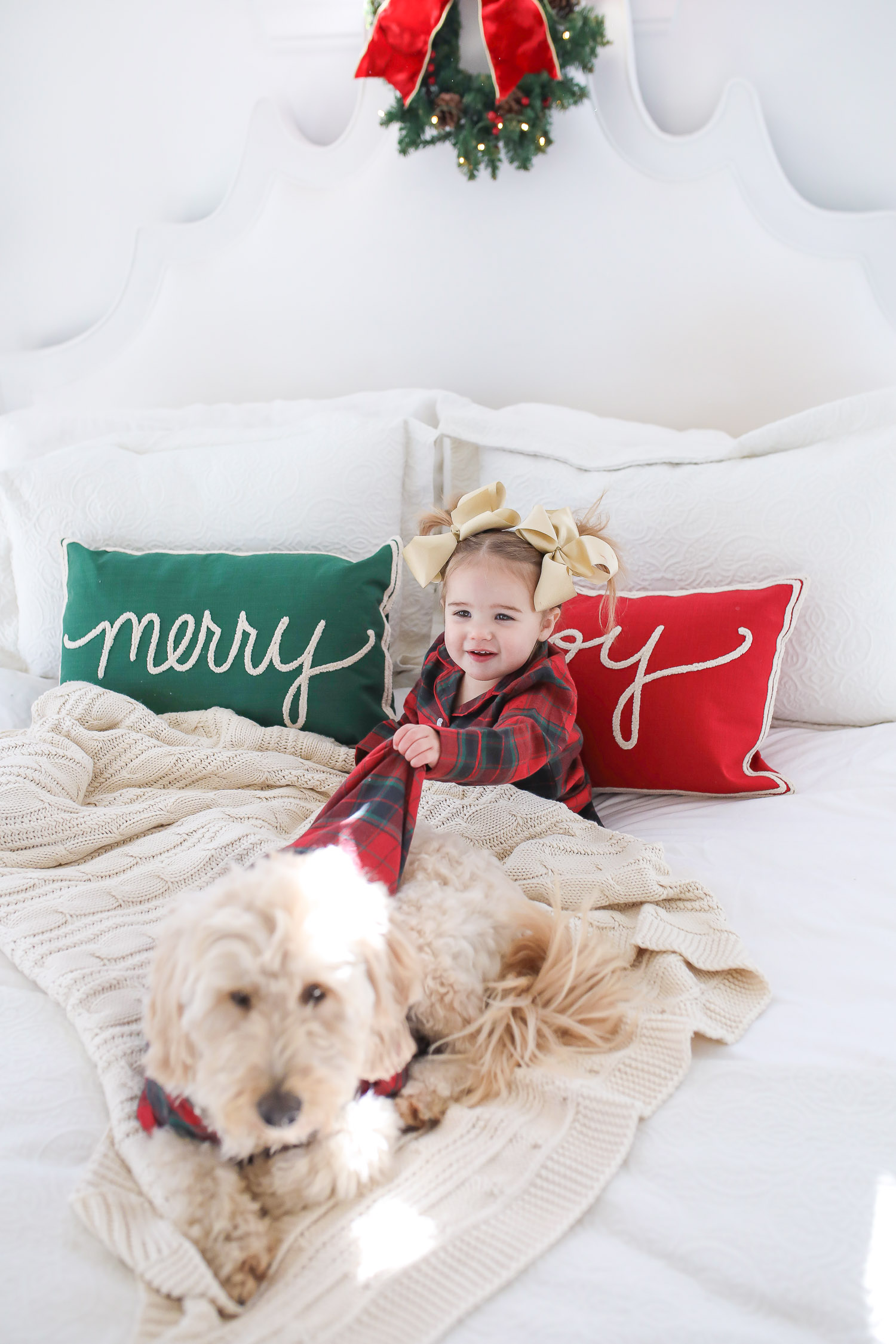 Matching Family Pajamas by popular US fashion blog, The Sweetest Thing: image of a young girl and her dog sitting on a bed with white bedding, a joy throw pillow, a merry throw pillow and a mini Christmas wreath hanging on the headboard and wearing a The Company Store Family Flannel Company Cotton™ Girls' Sleepshirt and The Company Store Family Flannel Company Cotton™ Dog Pajamas.