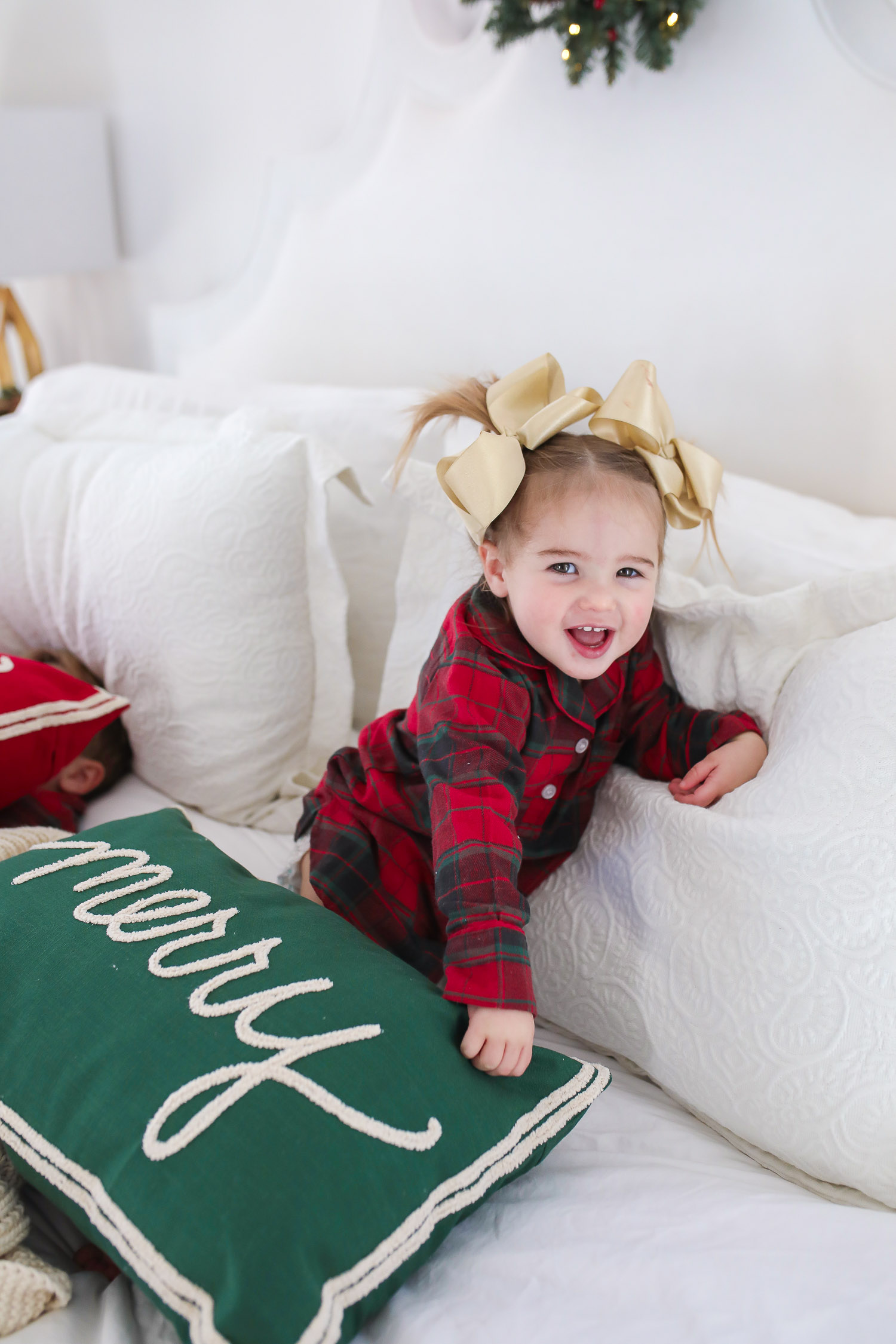 Matching Family Pajamas by popular US fashion blog, The Sweetest Thing: image of a young girl sitting on a bed with white bedding, a joy throw pillow, a merry throw pillow and a mini Christmas wreath hanging on the headboard and wearing a The Company Store Family Flannel Company Cotton™ Girls' Sleepshirt.