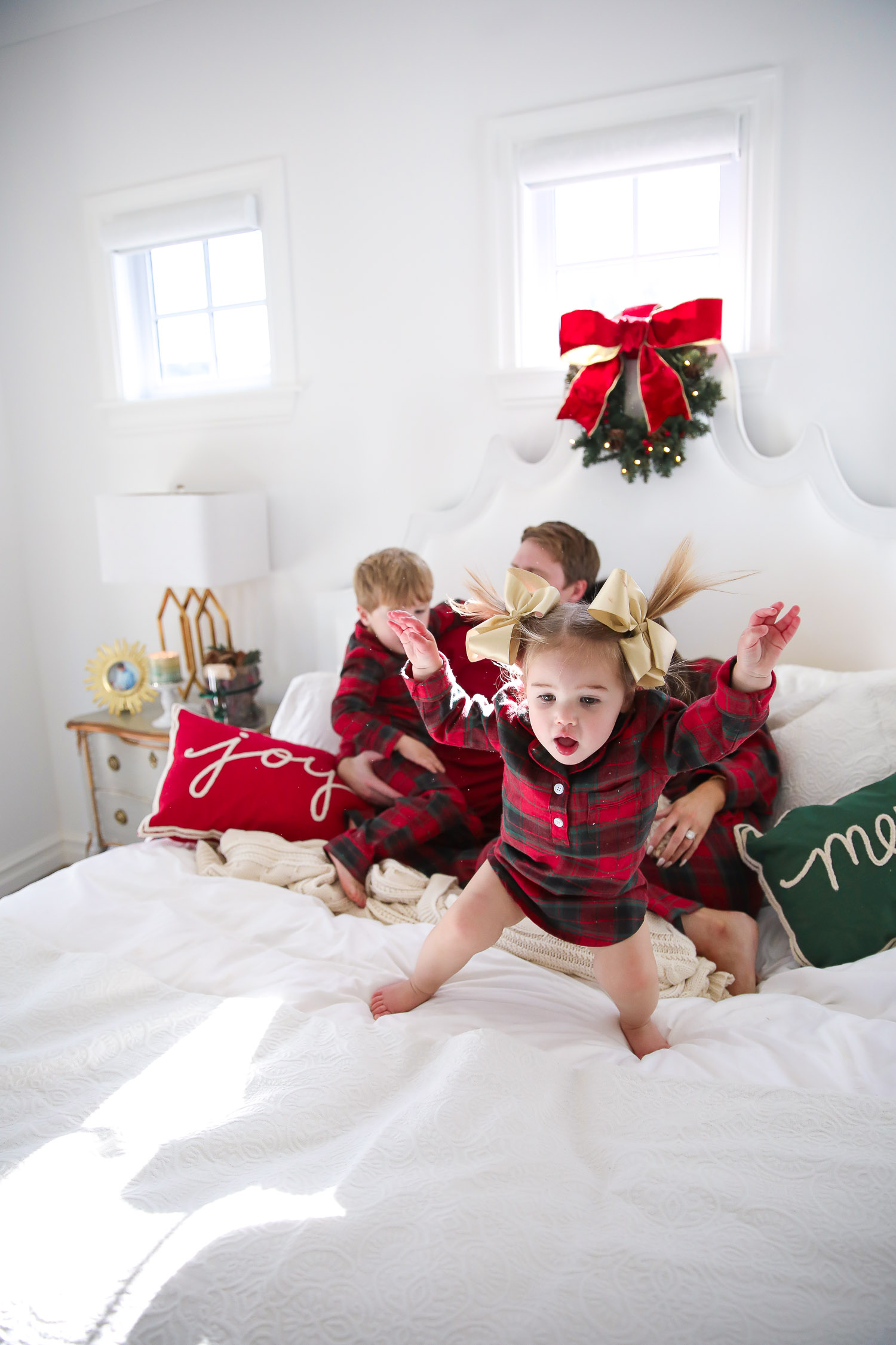 Matching Family Pajamas by popular US fashion blog, The Sweetest Thing: image of a family sitting on a bed with white bedding, a joy throw pillow, a merry throw pillow and a mini Christmas wreath hanging on the headboard and wearing a The Company Store Family Flannel Company Cotton™ Womens Pajama Set, The Company Store Family Flannel Company Cotton™ Girls' Sleepshirt, The Company Store Family Flannel Company Cotton™ Kids' Pajama Set, The Company Store Family Flannel Company Cotton™ Mens Pajama Set, and The Company Store Family Flannel Company Cotton™ Dog Pajamas.
