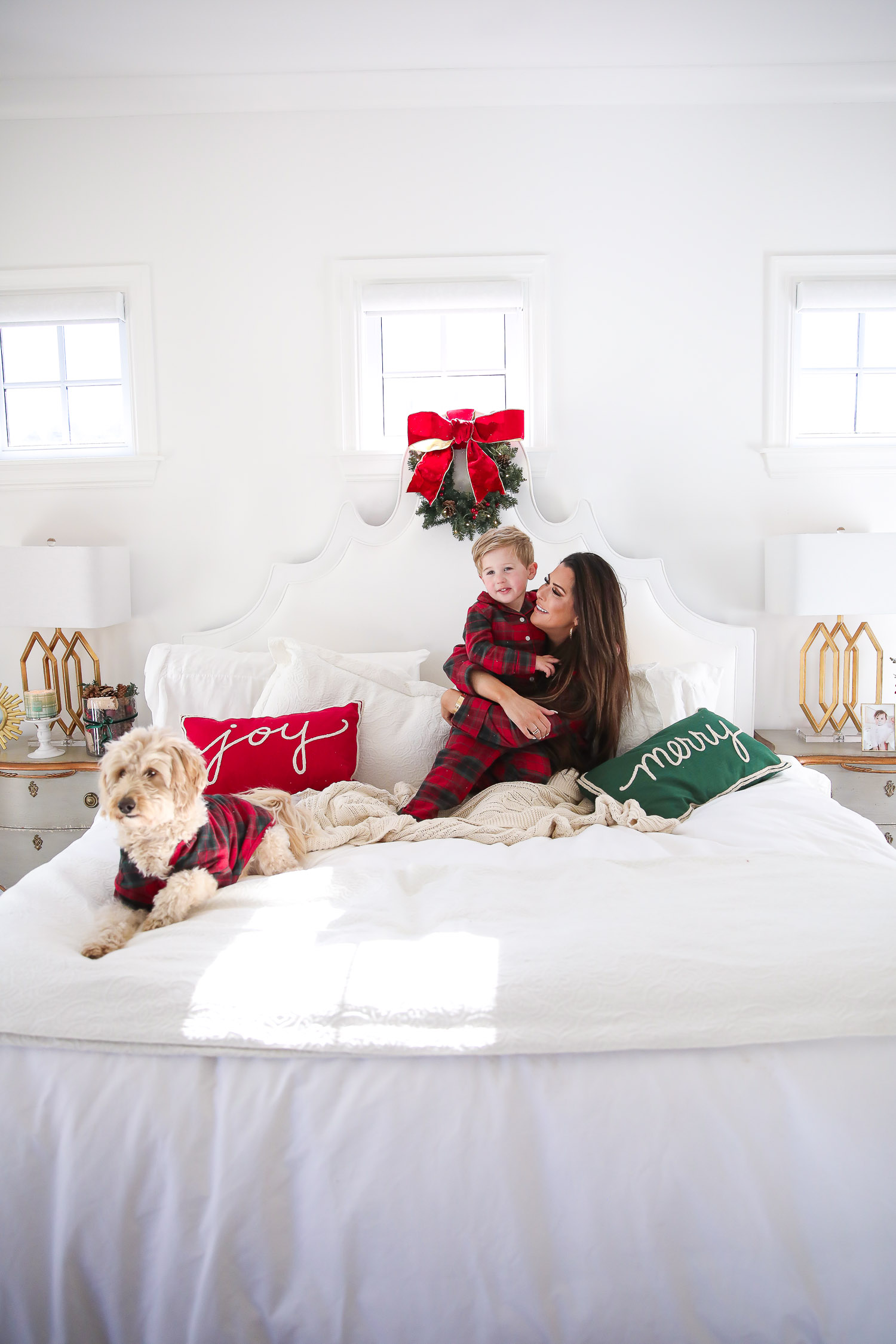 Matching Family Pajamas by popular US fashion blog, The Sweetest Thing: image of a Emily Gemma and her son sitting on a bed with white bedding, a joy throw pillow, a merry throw pillow and a mini Christmas wreath hanging on the headboard with their dog and wearing a The Company Store Family Flannel Company Cotton™ Womens Pajama Set, The Company Store Family Flannel Company Cotton™ Kids' Pajama Set, and The Company Store Family Flannel Company Cotton™ Dog Pajamas.