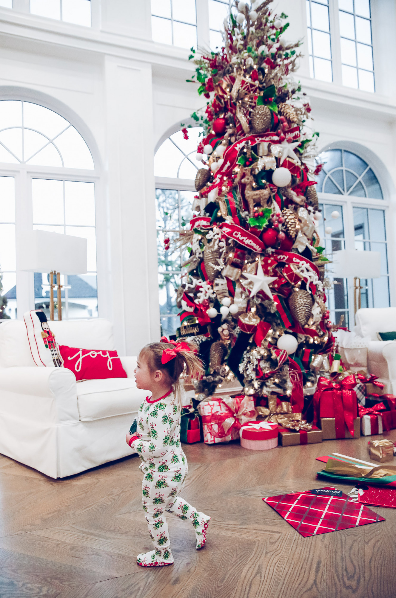 walmart gift wrap christmas 2020, shop hello holidays christmas tree, magnetic me PJs, emily ann gemma-10 |Gift Wrapping Ideas by popular US life and style blog, The Sweetest Thing: image of a little girl wearing Magnetic Me Christmas pjs while standing next to Christmas wrapping paper spread all over the floor in front of a Christmas tree with red, green and gold ornaments.