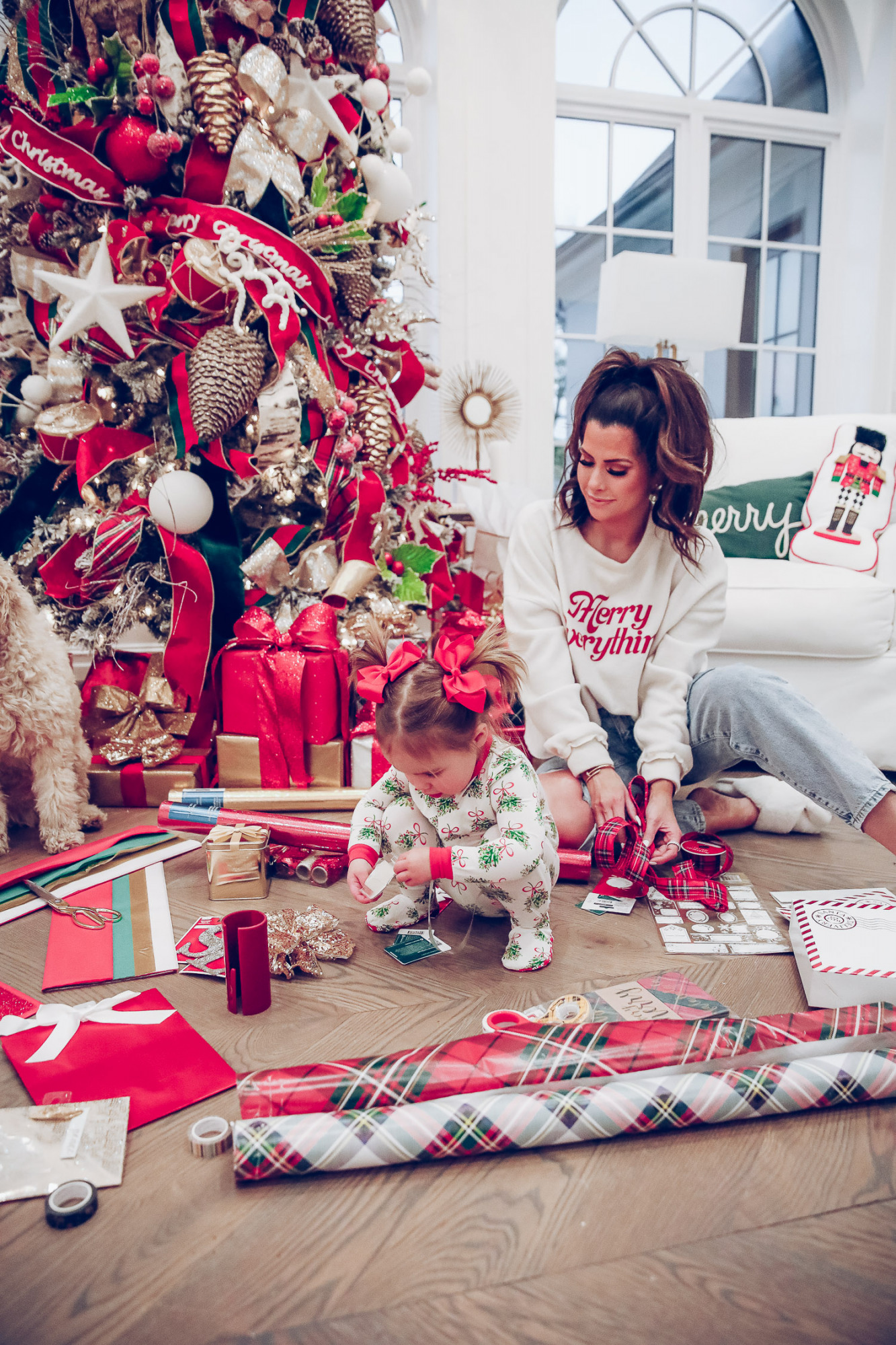 walmart gift wrap christmas 2020, shop hello holidays christmas tree, magnetic me PJs, emily ann gemma-10 |Gift Wrapping Ideas by popular US life and style blog, The Sweetest Thing: image of a woman wearing a Merry Everything sweatshirt and her daughter wearing Magnetic Me Christmas pjs and sitting on the floor in front of their Christmas tree and next to Christmas wrapping paper supplies.
