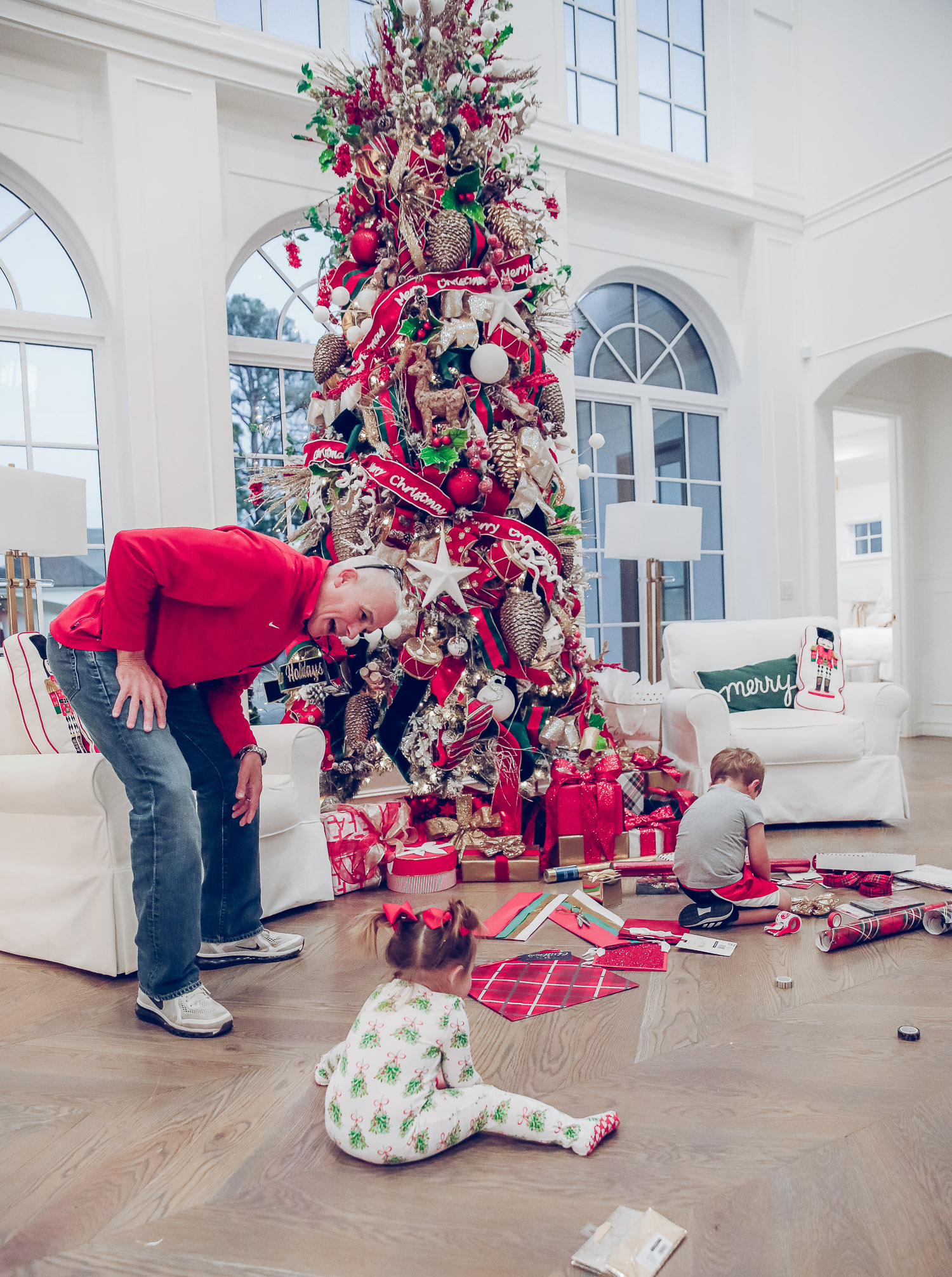 walmart gift wrap christmas 2020, shop hello holidays christmas tree, magnetic me PJs, emily ann gemma-10 |Gift Wrapping Ideas by popular US life and style blog, The Sweetest Thing: image of a little girl wearing Magnetic Me Christmas pjs sitting on the floor with her brother  while using Christmas wrapping paper supplies spread out on the floor in front of their Christmas tree.