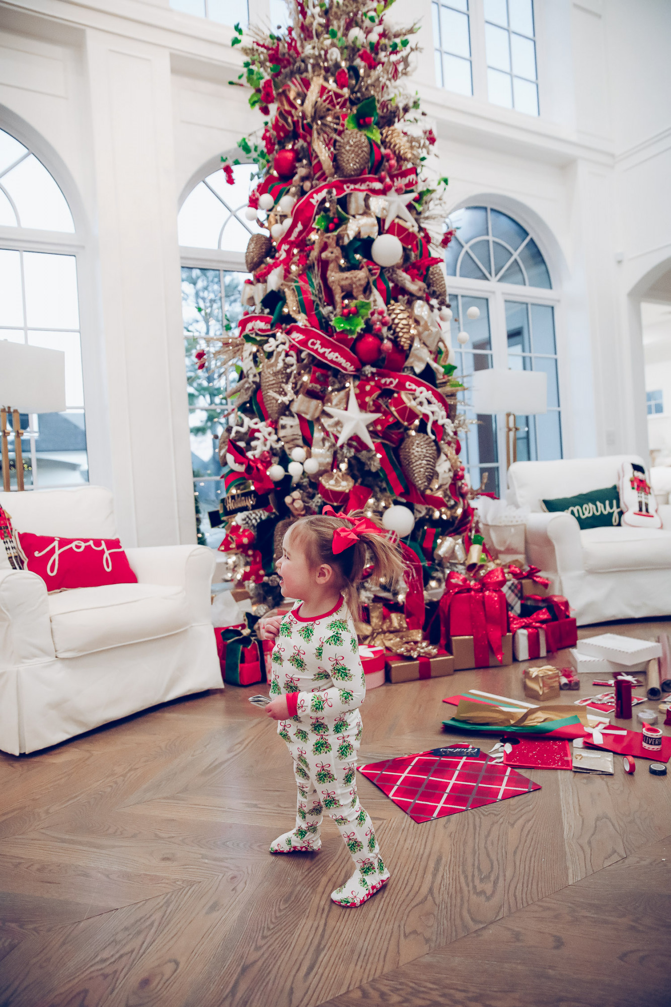 walmart gift wrap christmas 2020, shop hello holidays christmas tree, magnetic me PJs, emily ann gemma-10 | Gift Wrapping Ideas by popular US life and style blog, The Sweetest Thing: image of a little girl wearing Magnetic Me Christmas pjs while standing next to Christmas wrapping paper spread all over the floor in front of a Christmas tree with red, green and gold ornaments.