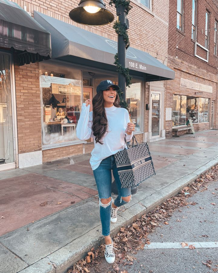 white long sleeve shirt, best white t-shirt 2021, ripped jeans, NY baseball cap, christian dior sneakers, christian dior tote bag, Emily Gemma