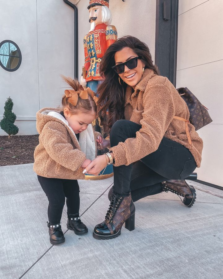 mommy and me outfit ideas, Louis Vuitton backpack, Louis Vuitton star trail ankle boot, black denim, sunglasses, gold hoop earrings