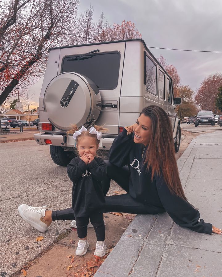 November Instagram Recap by popular US lifestyle blog, The Sweetest Thing: image of Emily Gemma sitting on a curb with her daughter Sophie and wearing a pair of black Spanx leggings, black Dior sweatshirt, white platform sneakers, and Gorjana necklace.