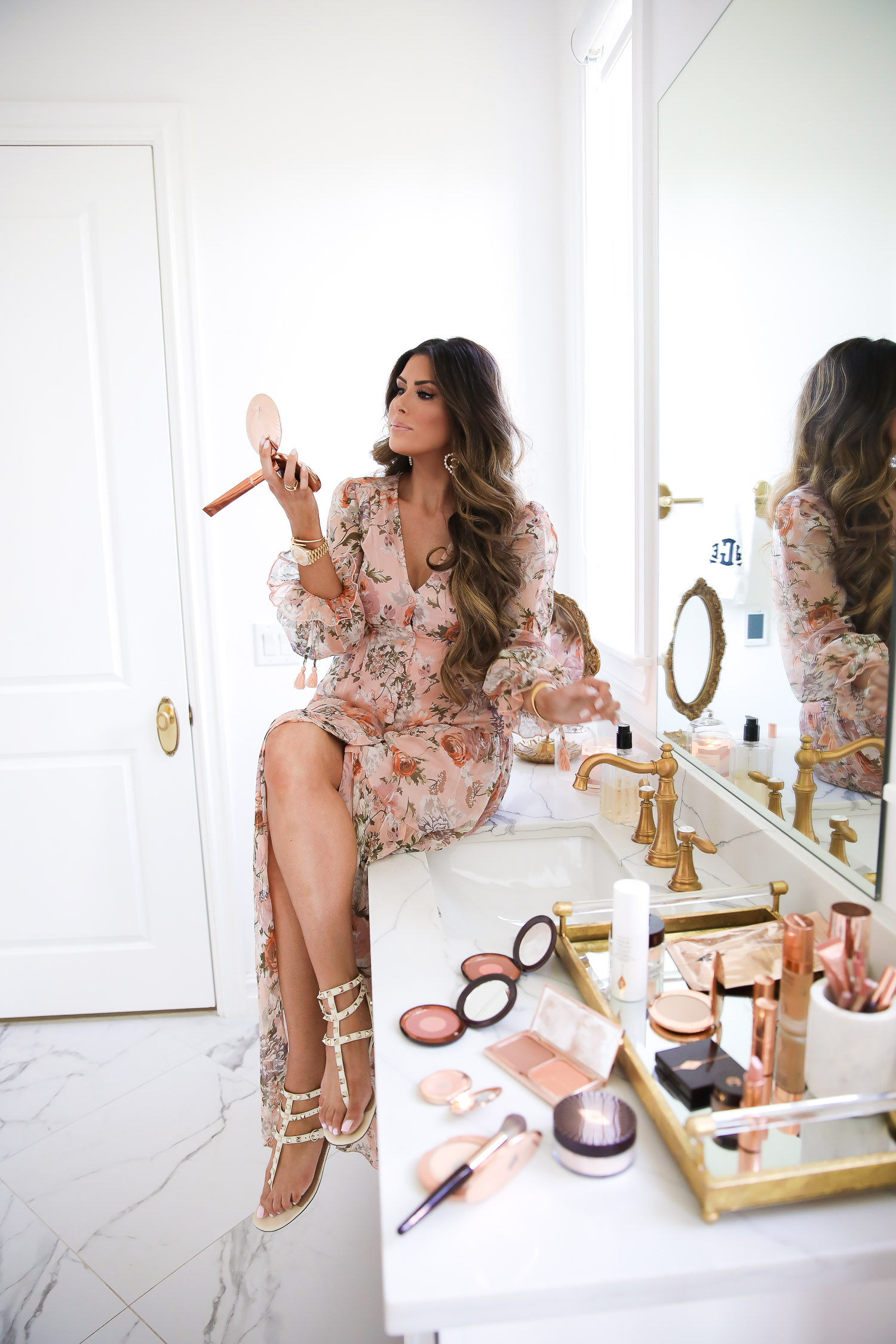 Top Picks by popular US life and style blog, The Sweetest Thing: image of Emily Gemma wearing a floral puff sleeve dress and sitting on her bathroom vanity while holding and looking in to a compact mirror.