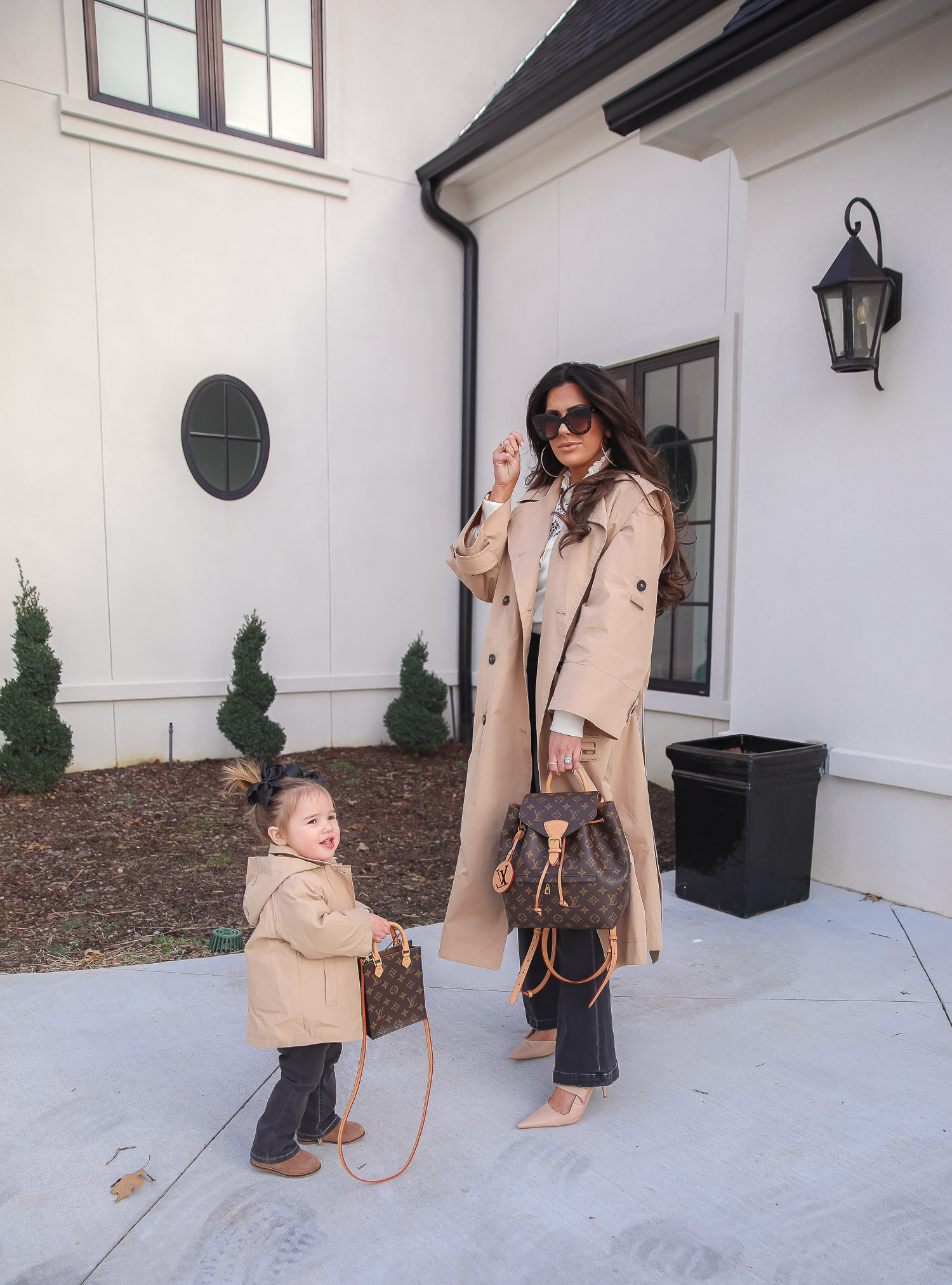 Express spring fashion 2021, emily gemma, mommy daughter matching outfits pinterest, baby fashion blogger, express trench coat 2021 | Mommy and Me Outfits by popular US fashion blog, The Sweetest Thing: image of Emily Gemma and her daughter Sophie standing outside and wearing a Express trench coat, Express flare jeans, Express gold hoop earrings, Express ruffle lack mock neck shirt, and holding a Louis Vuitton bags.