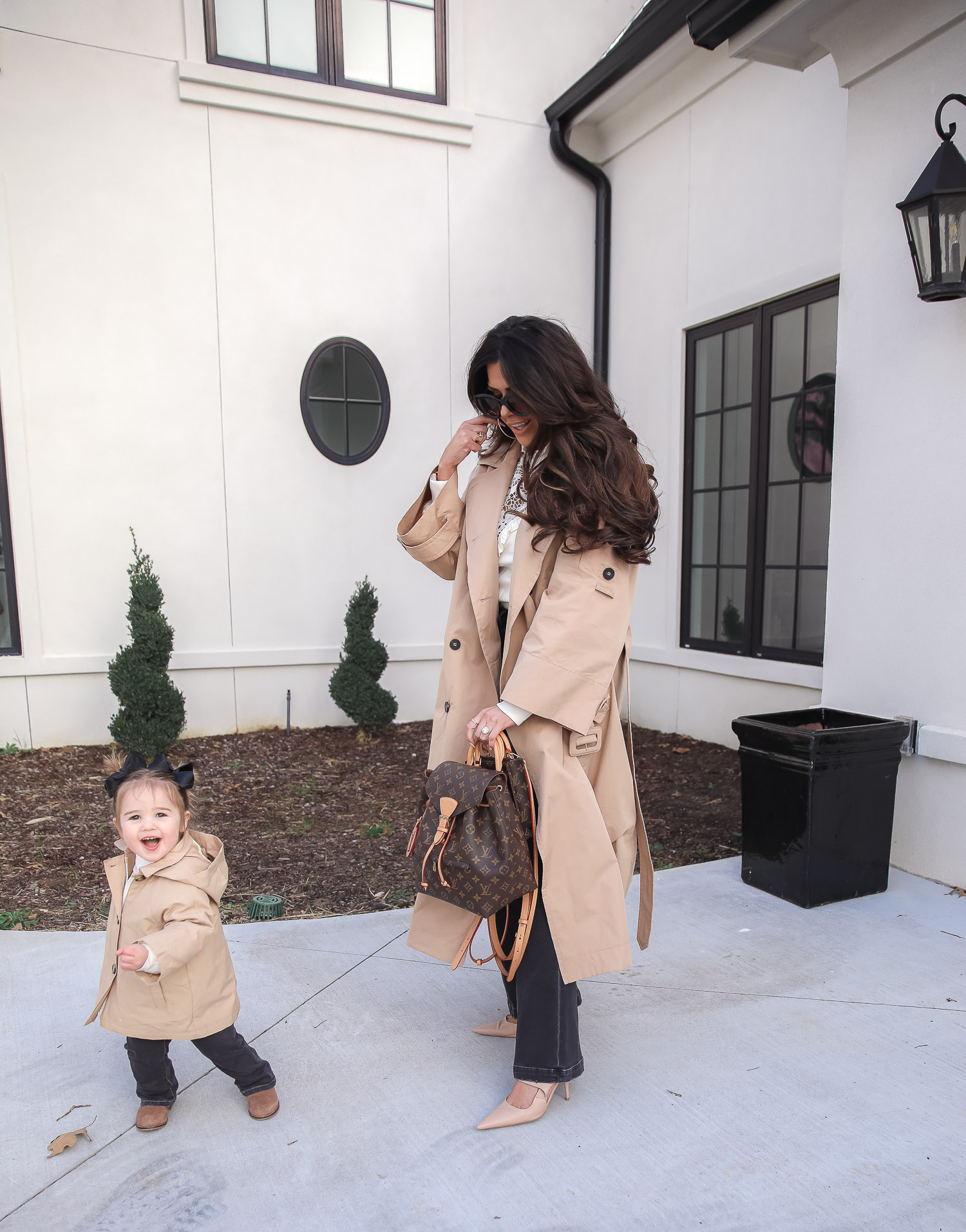 Express spring fashion 2021, emily gemma, mommy daughter matching outfits pinterest, baby fashion blogger, express trench coat 2021 |Mommy and Me Outfits by popular US fashion blog, The Sweetest Thing: image of Emily Gemma and her daughter Sophie standing outside and wearing a Express trench coat, Express flare jeans, Express gold hoop earrings, Express ruffle lack mock neck shirt, and holding a Louis Vuitton bags.