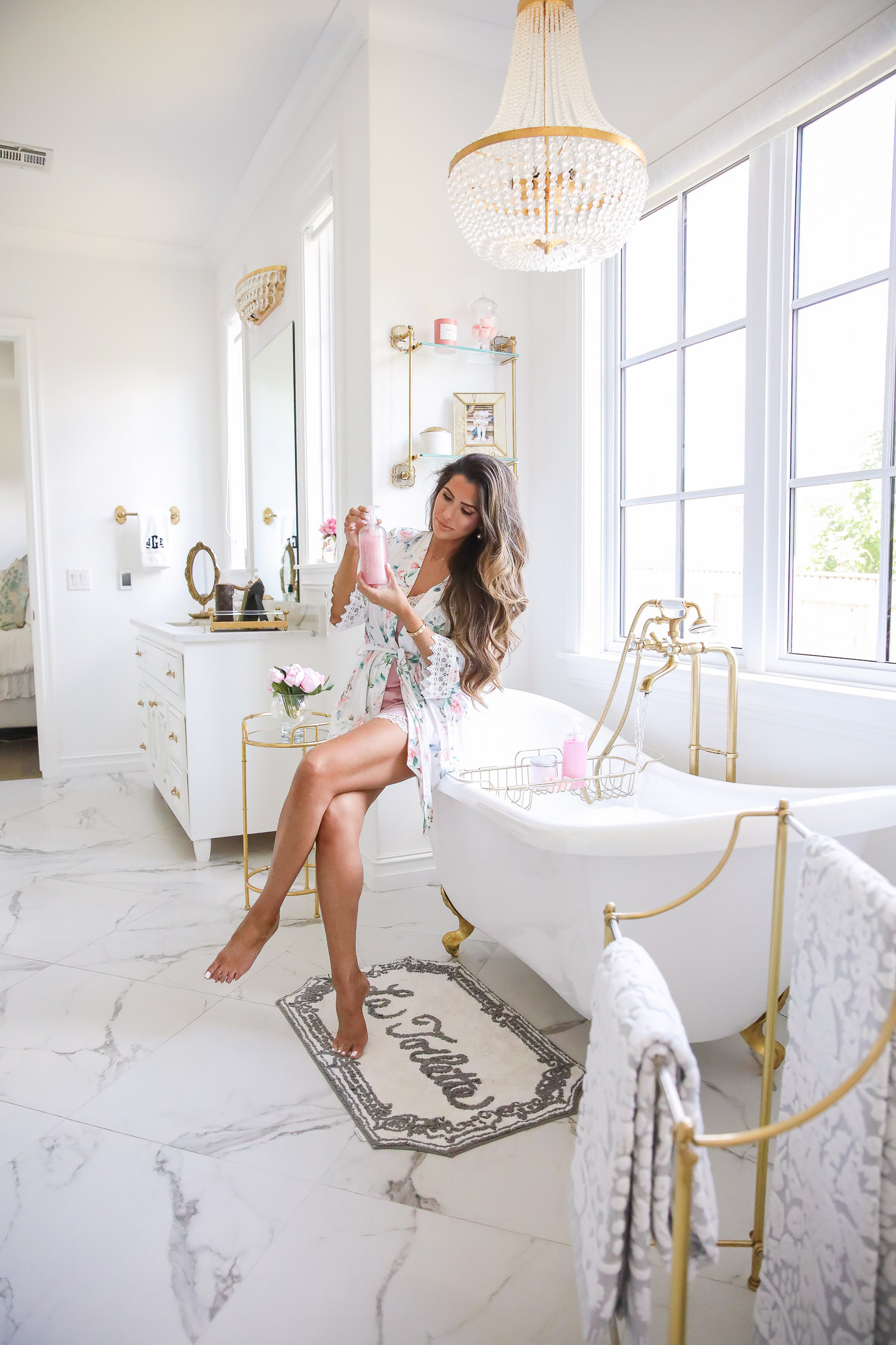 Top Picks by popular US life and style blog, The Sweetest Thing: image of Emily Gemma wearing a floral robe and sitting on the edge of her white and gold clawfoot tub and holding a bottle of body wash.