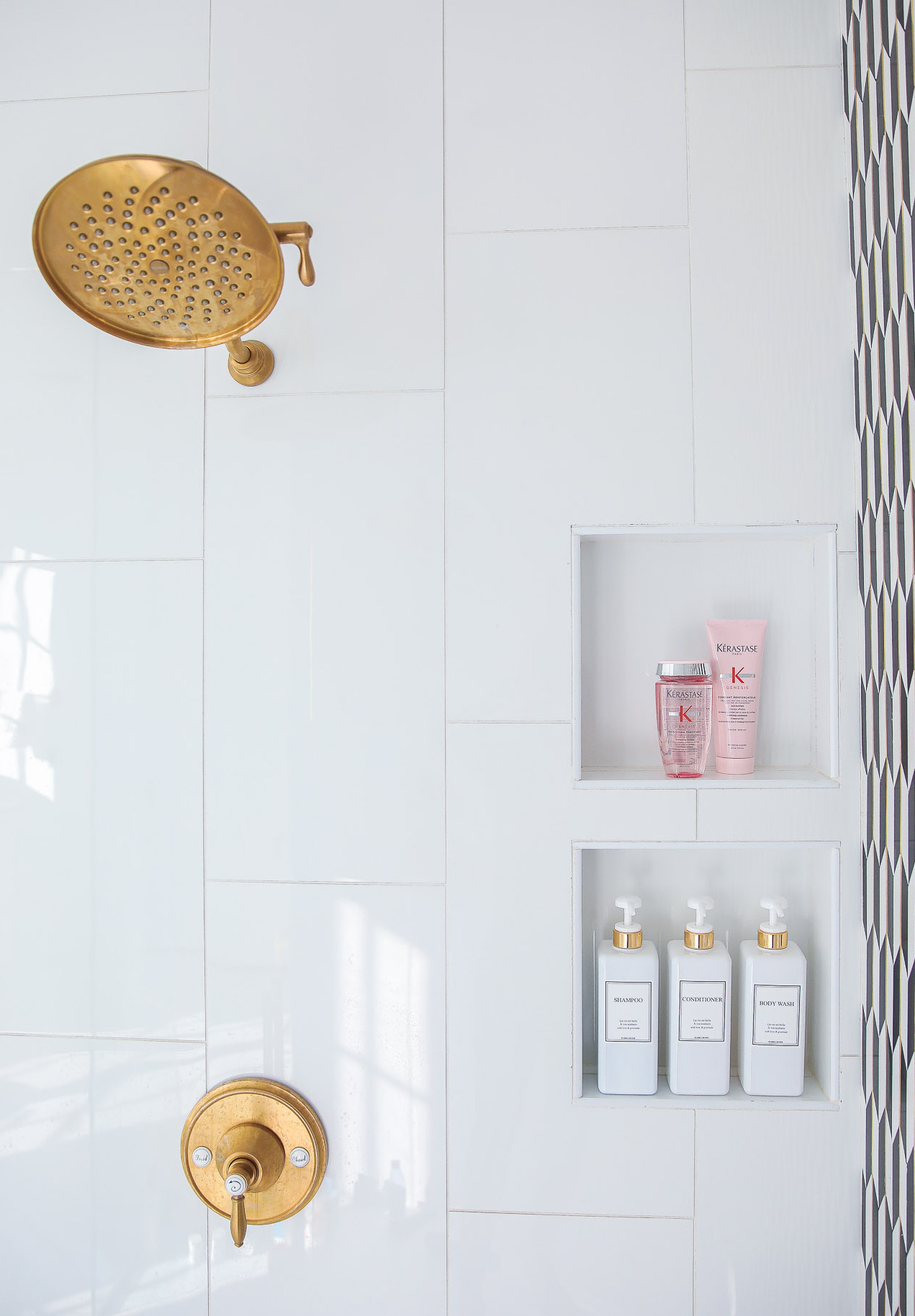 Top Picks by popular US life and style blog, The Sweetest Thing: image of Kerastase products in a white tile shower with a a gold faucet and gold shower head.