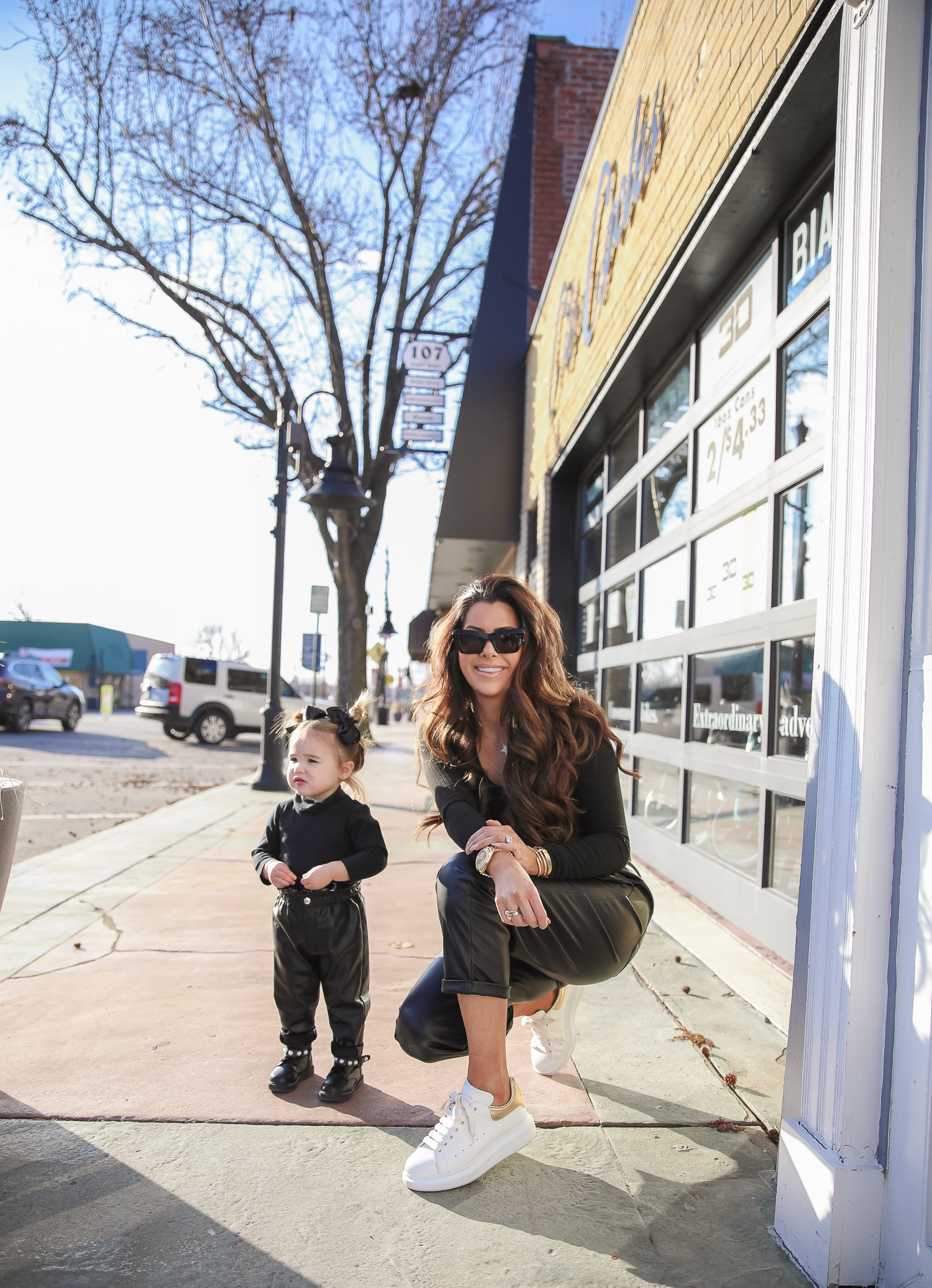 Nordstrom BP faux leather pants, loewe sunglasses, Alexander mcqueen sneakers gold white outfit pinterest, matching mommy daughter fashion, emily gemma |Mommy and Daughter by popular US fashion blog, The Sweetest Thing: image of a woman and her daughter walking together outside and wearing a pair of BP faux leather pants, Good American top, loewe sunglasses, Alexander mcqueen sneakers, Monica Vinader ring, Nadri bracelet, Nadri earrings, and Rolex watch.