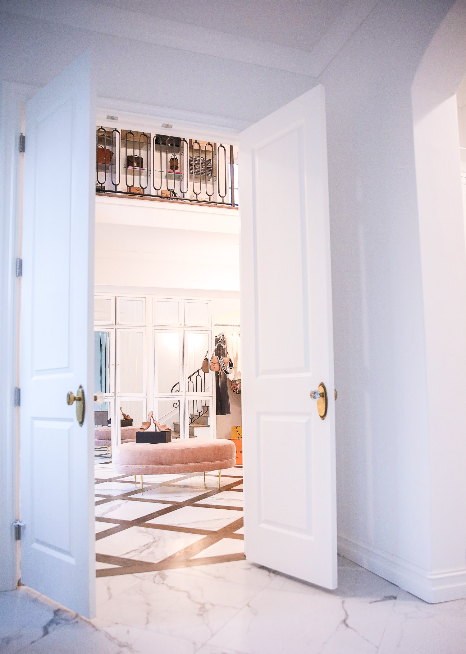 Top Picks by popular US life and style blog, The Sweetest Thing: image of a two story closet with white double doors, gold and crystal door knobs, marble and wood flooring, black metal stair railing, full length mirrors, and a pink velvet ottoman.