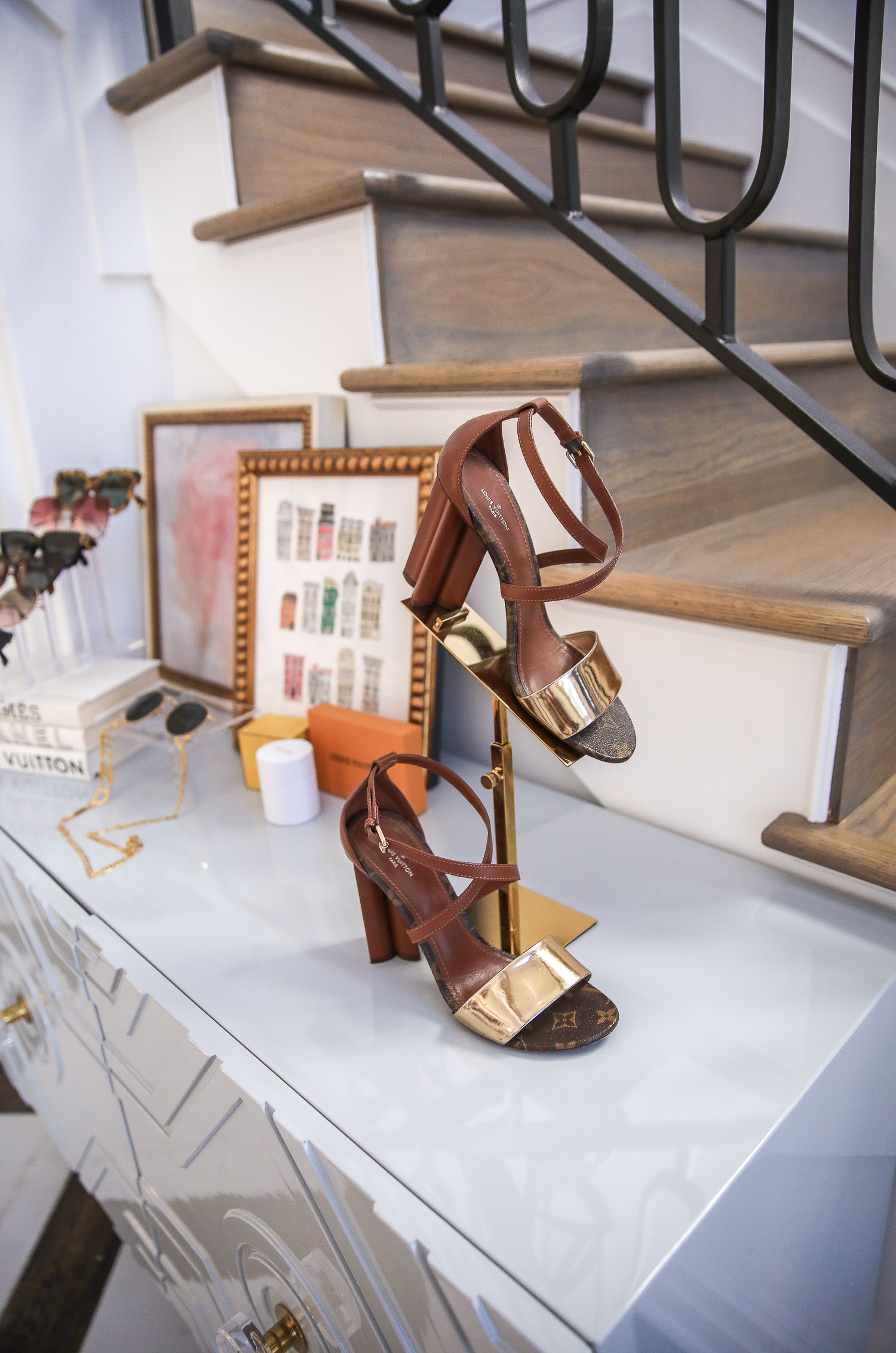 Top Picks by popular US life and style blog, The Sweetest Thing: image of Louis Vuitton sandals on a gold shoe stand.