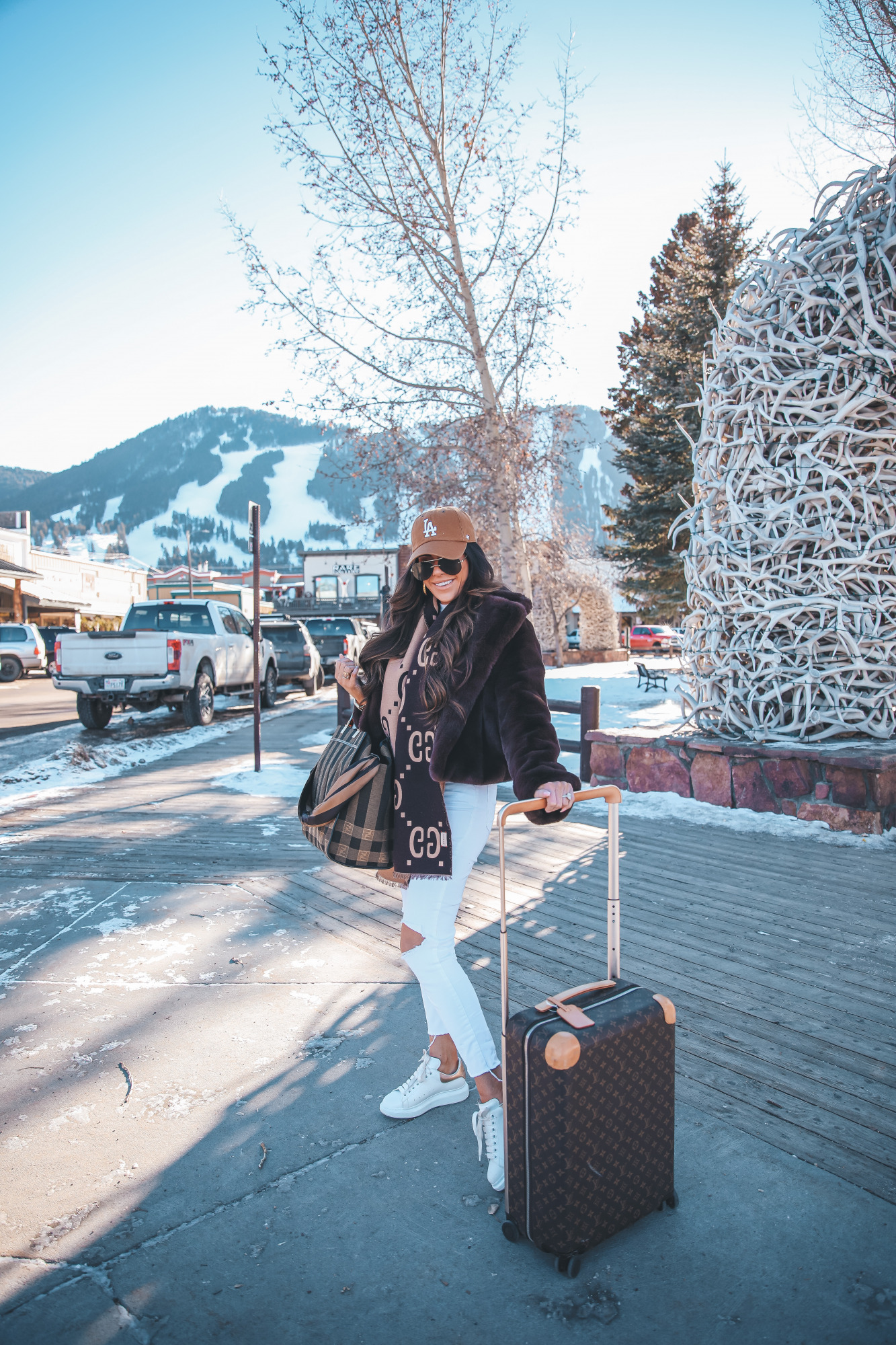 casual travel outfit idea winter 2021, airport fashion outfit idea, cute airport outfit idea winter, fendi tote | Winter Fashion by popular US fashion blog, The Sweetest Thing: image of Emily Gemma standing by the antler arch in Jackson Hole, WY and wearing a Free People top, BB Dakota faux fur jacket, distressed white denim jeans, Gucci scarf, '47 brand cap, Le Specs sunglasses, and standing next to a Louis Vuitton rolling suitcase and holding a Fendi tote bag.