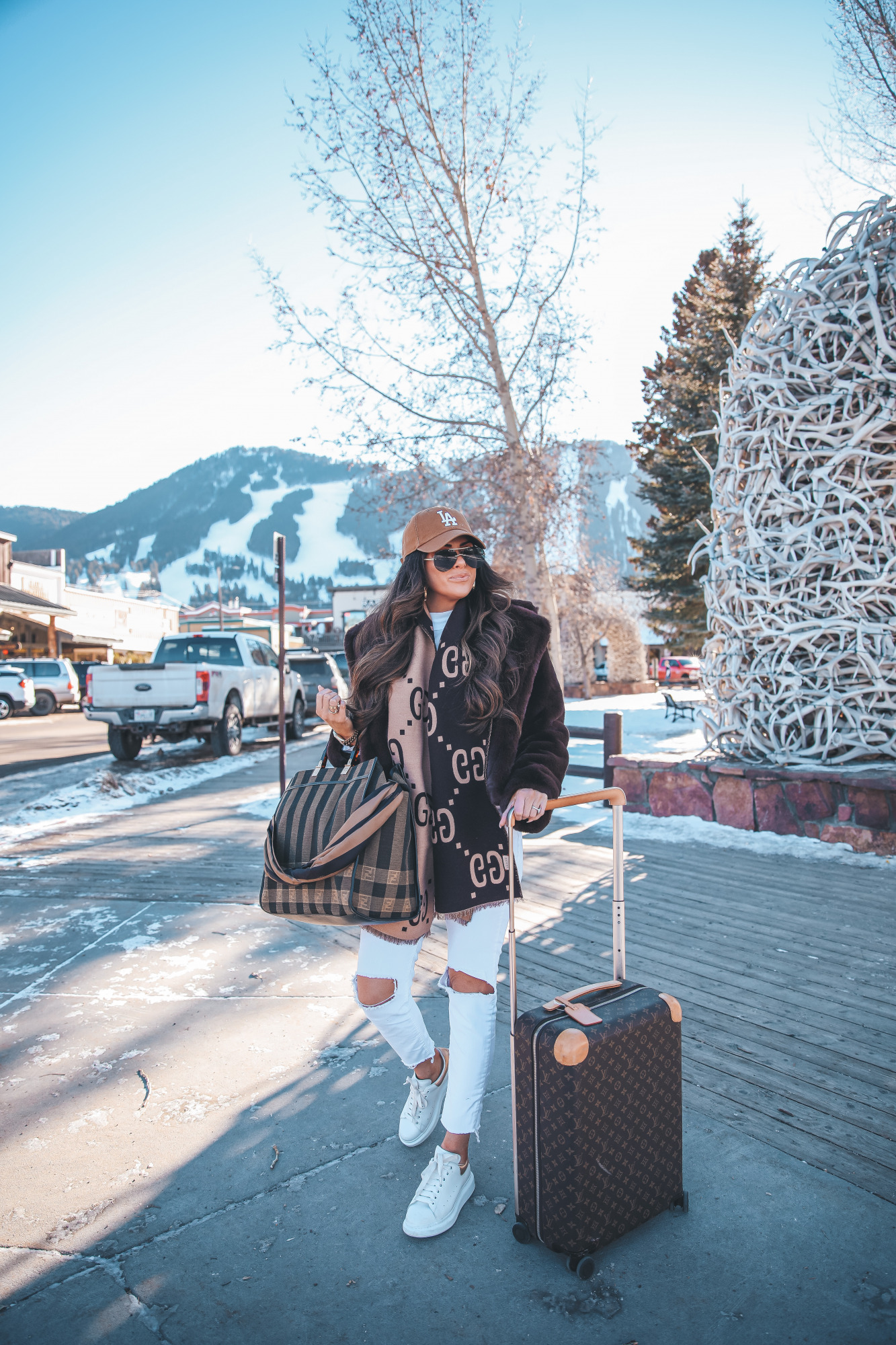 casual travel outfit idea winter 2021, airport fashion outfit idea, cute airport outfit idea winter, fendi tote |Winter Fashion by popular US fashion blog, The Sweetest Thing: image of Emily Gemma standing outside in downtown Jackson Hole, WY and wearing a Free People top, BB Dakota faux fur jacket, distressed white denim jeans, Gucci scarf, '47 brand cap, Le Specs sunglasses, and standing next to a Louis Vuitton rolling suitcase and holding a Fendi tote bag.