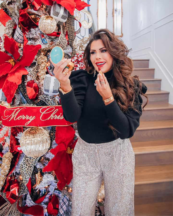 November Instagram Recap by popular US lifestyle blog, The Sweetest Thing: image of Emily Gemma wearing a Express puff sleeve turtleneck top and Express sequin pants while standing next to a Christmas tree and applying red lipstick while looking in a gold and blue compact mirror.