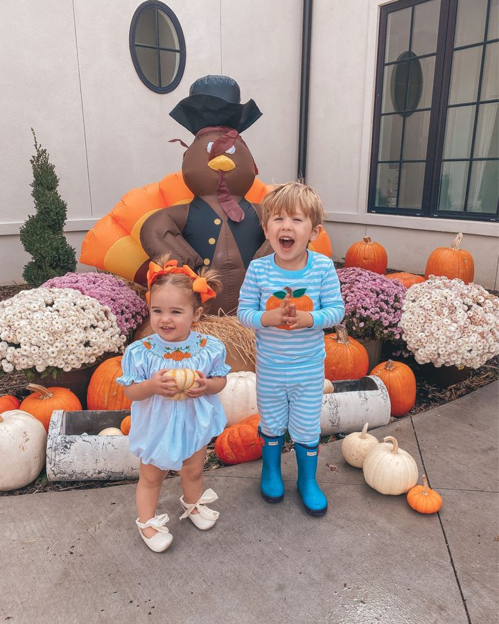 November Instagram Recap by popular US lifestyle blog, The Sweetest Thing: image of a young girl and a young boy standing in front of an inflatable turkey, potted mums, and orange and white pumpkins and wearing a blue romper, orange hair bows, cream bow tie shoes, blue and white stripe pumpkin pajamas, and blue hunter boots.