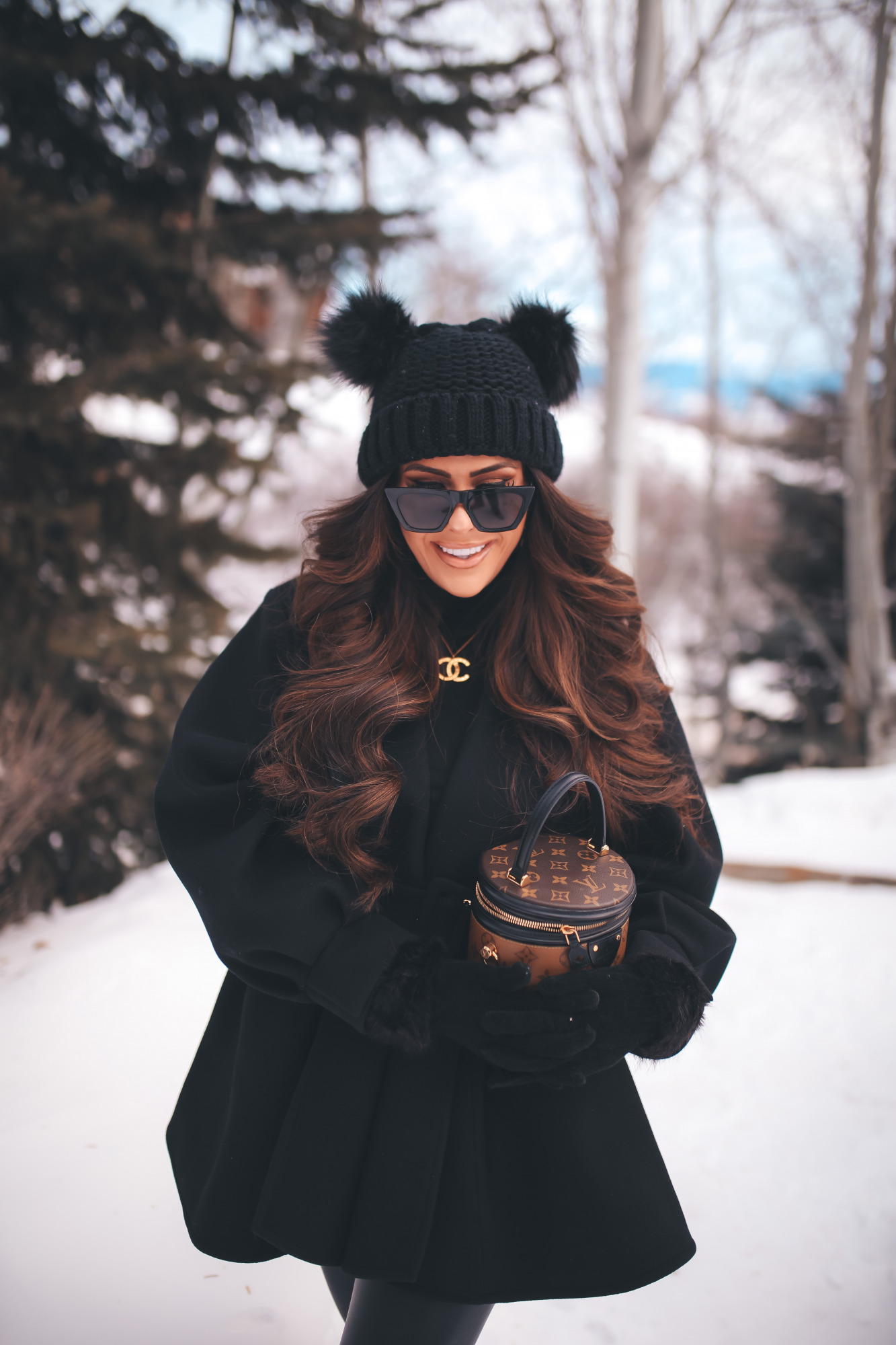 hair by chrissy extensions brunette balayage, louis vuitton cannes, jackson hole four seasons4 |Dressing Up by popular US fashion blog, The Sweetest Thing: image of Emily Gemma standing outside in the snow and wearing a Good American bodysuit, commando leggings, Chanel boots, Amazon sunglasses, Storets puff sleeve coat, Tasha double pom beanie, and holding a Louis Vuitton bag.