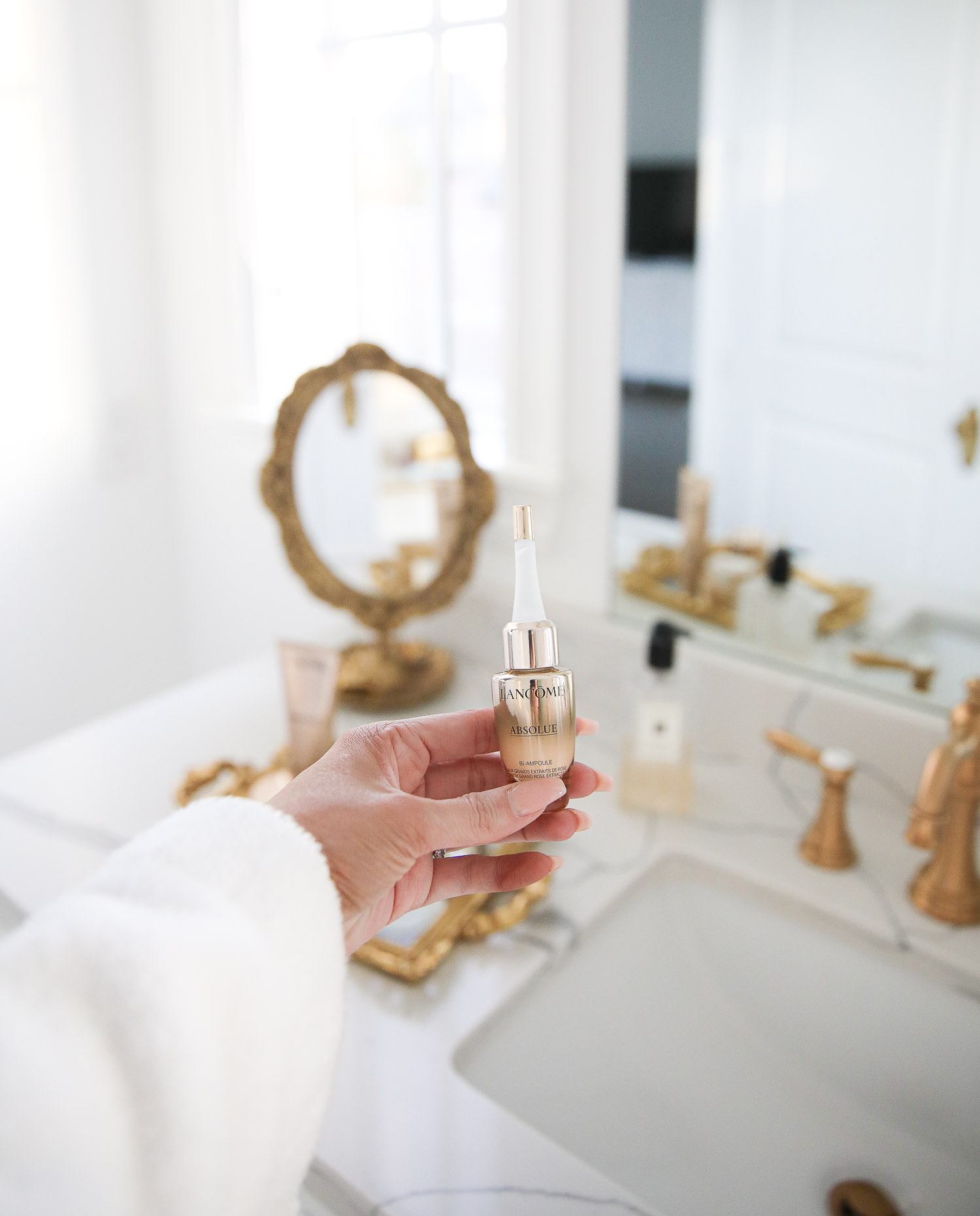 Lancome Skincare by popular US beauty blog, The Sweetest Thing: image of Emily Gemma holding a Lancome Absolue skincare product.